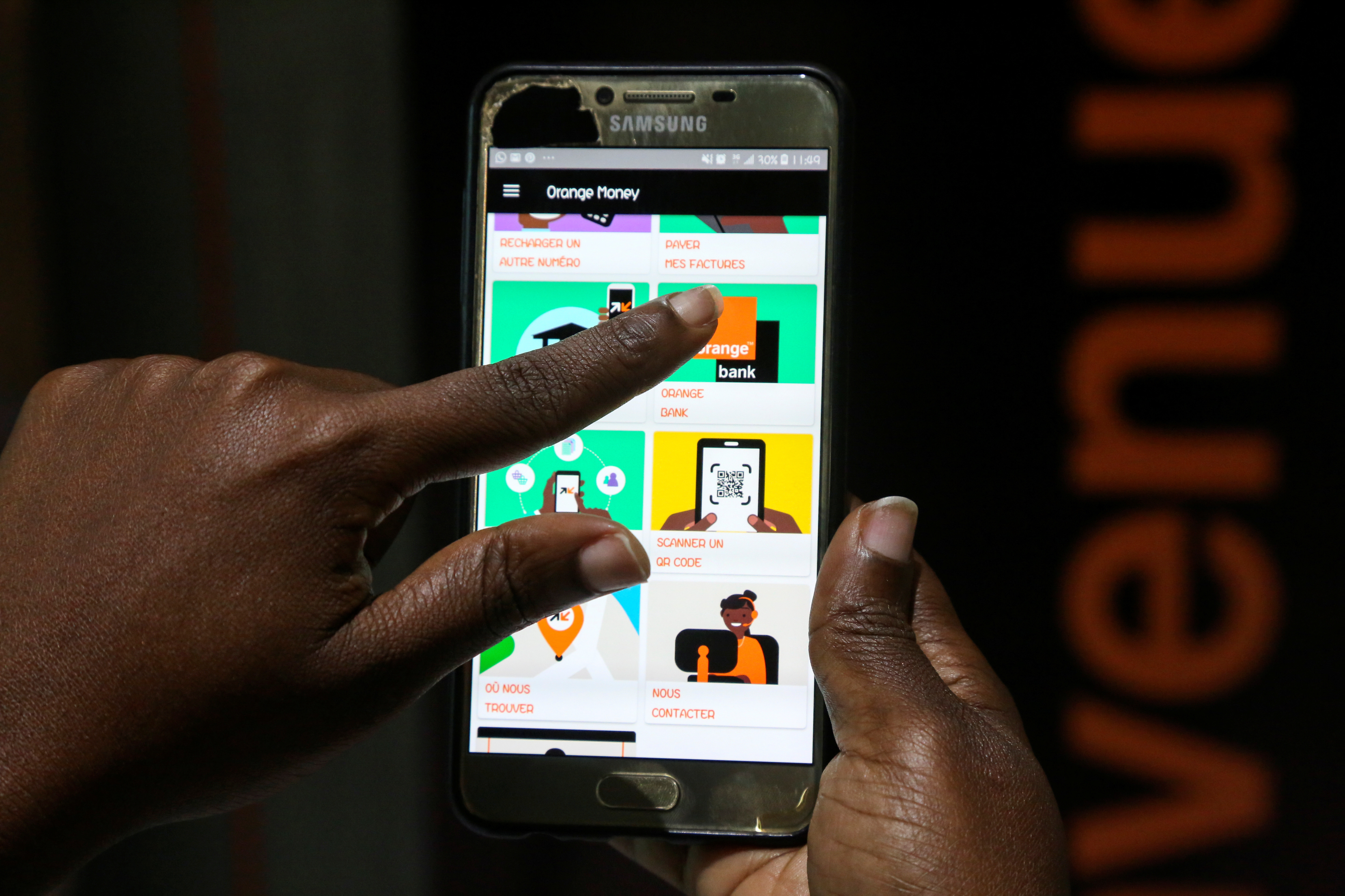 A woman prepares to perform a financial transaction on her mobile phone at a bank of the French mobile operator Orange in Abidjan, Ivory Coast, September 18, 2020. Picture taken September 18, 2020. REUTERS/Macline Hien - RC258J9G2FJF