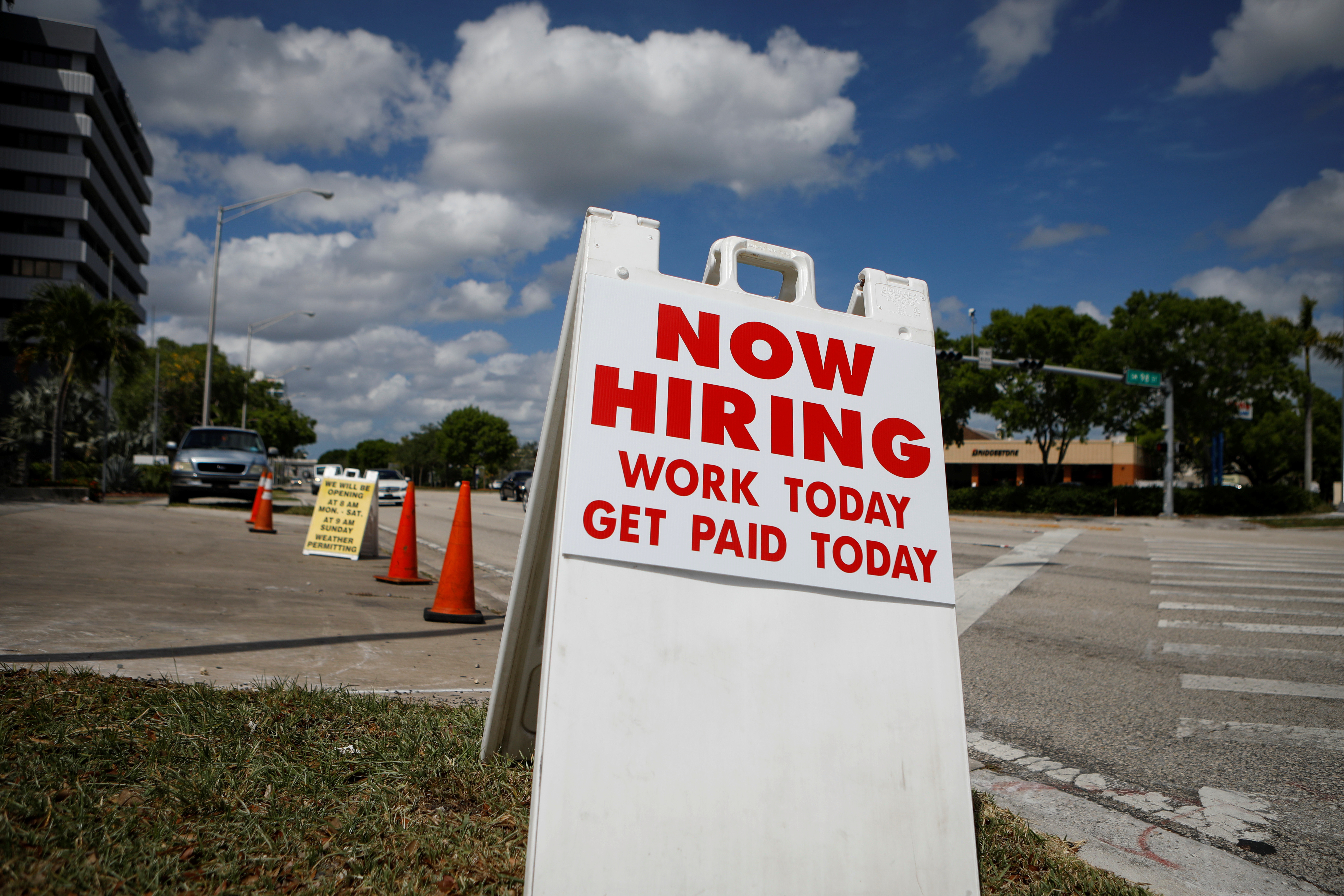 """A """"Now Hiring"""" sign advertising jobs at a hand car wash is seen along a street, as the spread of the coronavirus disease (COVID-19) continues, in Miami, Florida, U.S. May 8, 2020."""