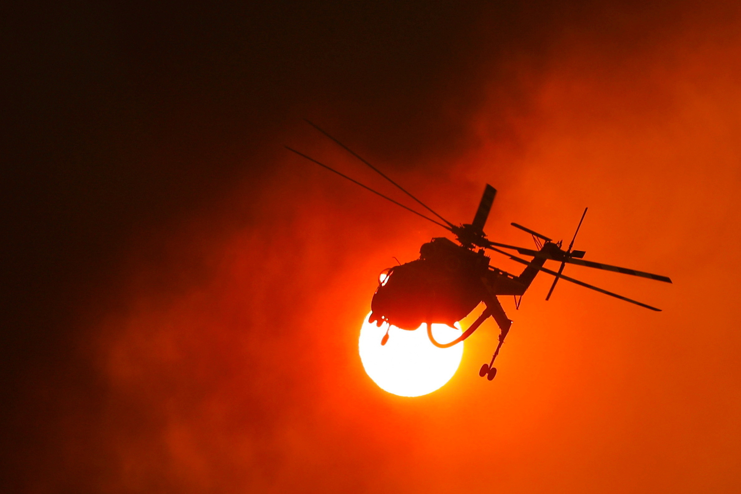 A firefighting helicopter flies by the sun as a wildfire burns in the village of Vilia, Greece, August 18, 2021. REUTERS/Alkis Konstantinidis     TPX IMAGES OF THE DAY - RC2S7P9DXFDE