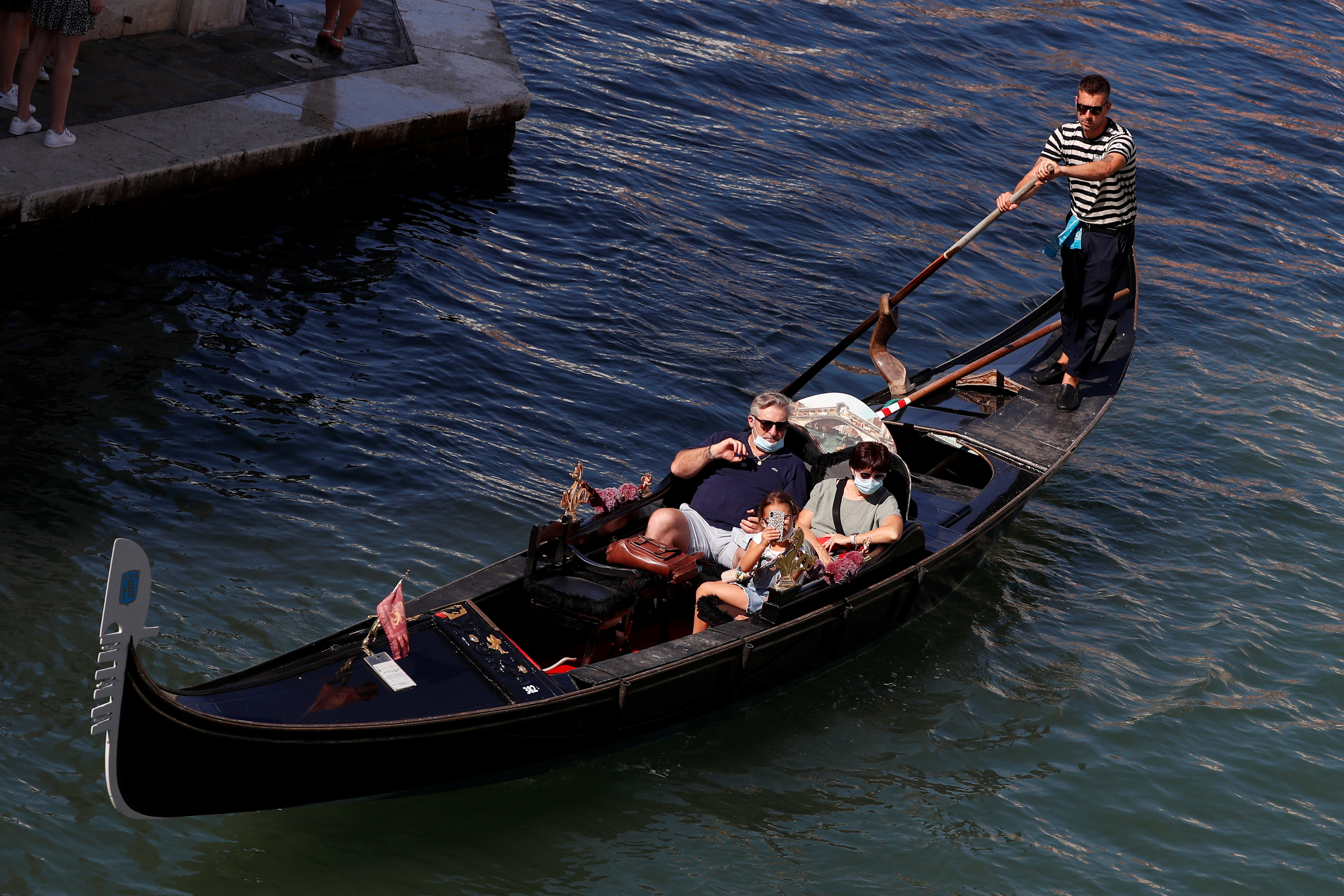 Tourists wear protective face masks as they take a gondola ride near Rialto bridge following the outbreak of the coronavirus disease (COVID-19) in Venice, Italy, September 9, 2020.