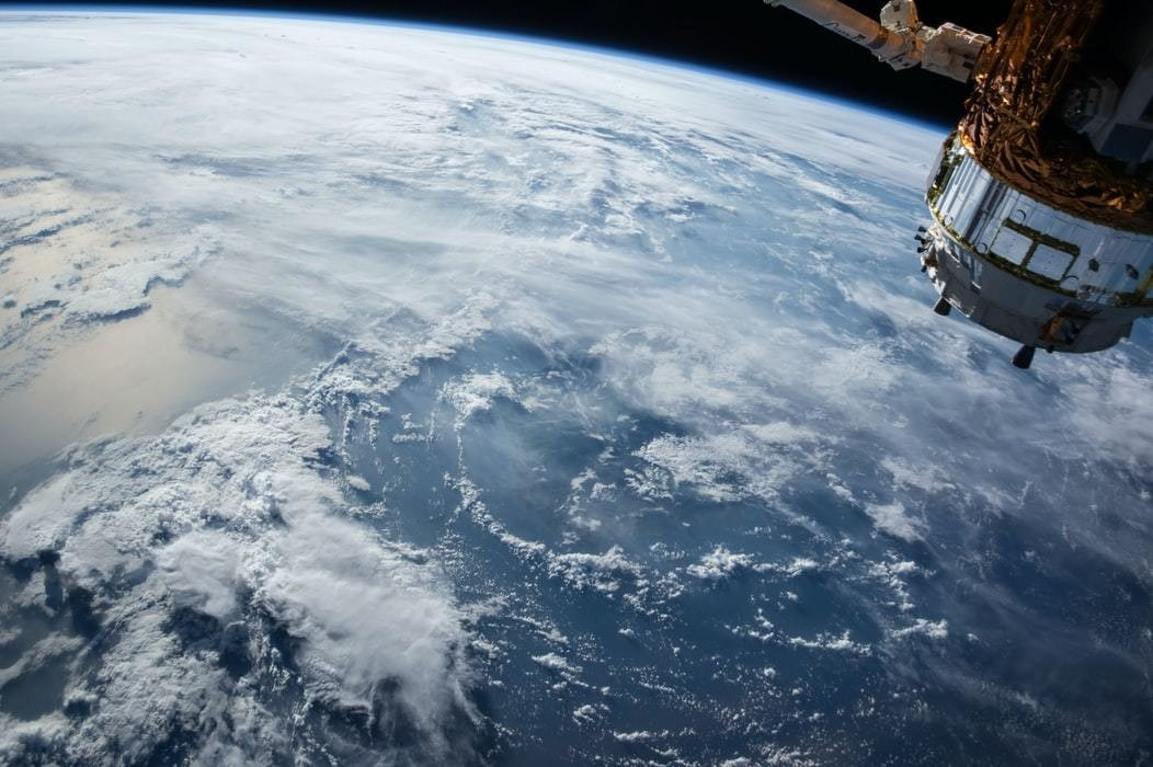 Ocean clouds seen from space with satellite in corner.