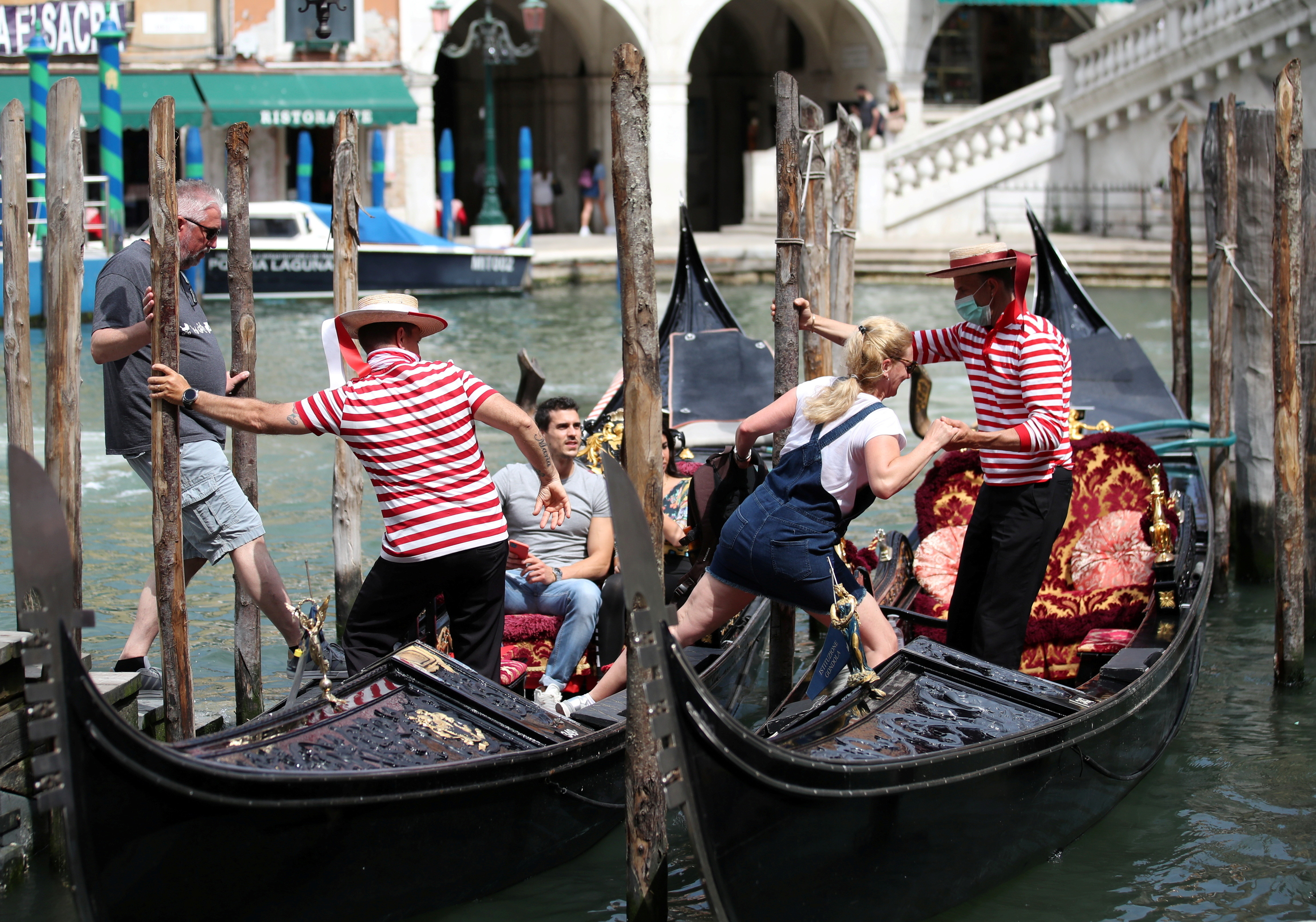 """Gondoliers help tourists to get on the gondolas, as the region of Veneto becomes a """"white zone"""", following a relaxation of COVID-19 restrictions with only masks and social distancing required, in Venice, Italy, June 7, 2021. REUTERS/Yara Nardi     TPX IMAGES OF THE DAY - RC2MVN9XRHN1"""