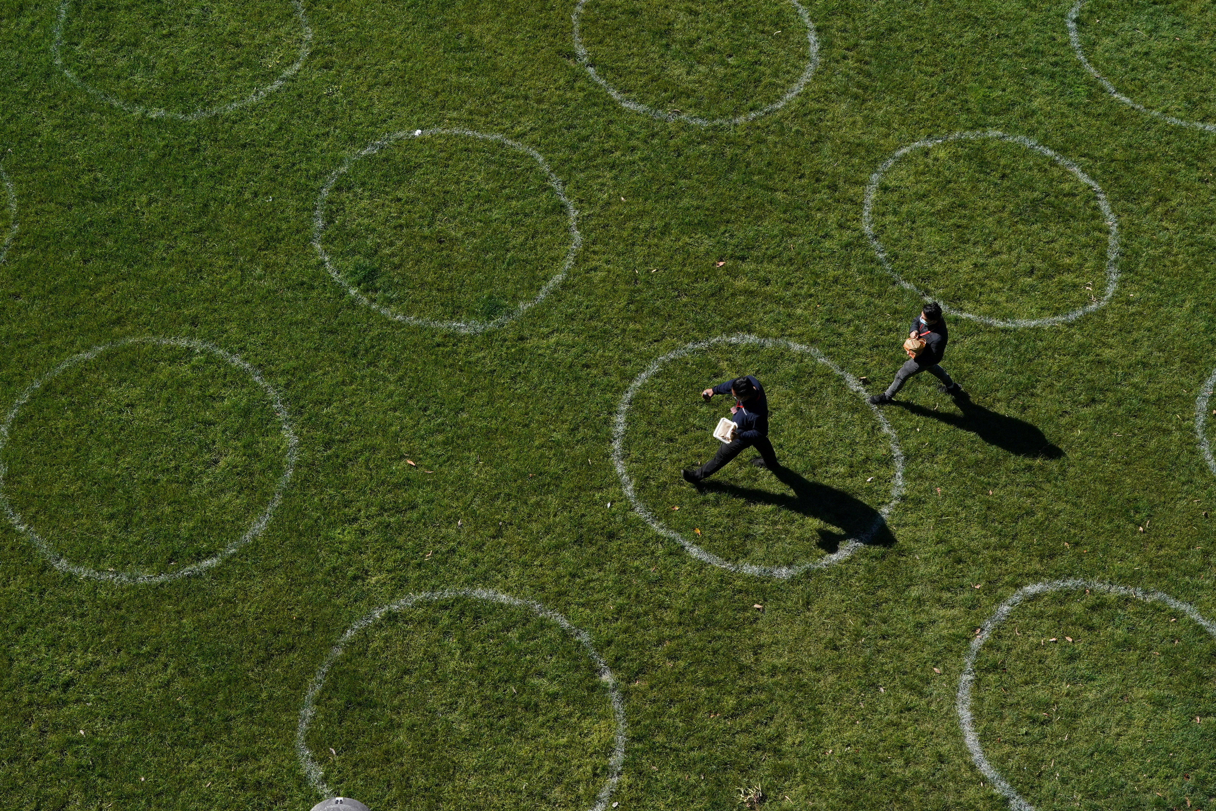 People walk through a city park marked with social distancing circles as some restrictions are eased for fully-vaccinated residents during a lockdown to curb the spread of a coronavirus disease (COVID-19) outbreak in Sydney, Australia, September 22, 2021.  REUTERS/Loren Elliott - RC2SUP95RC0O