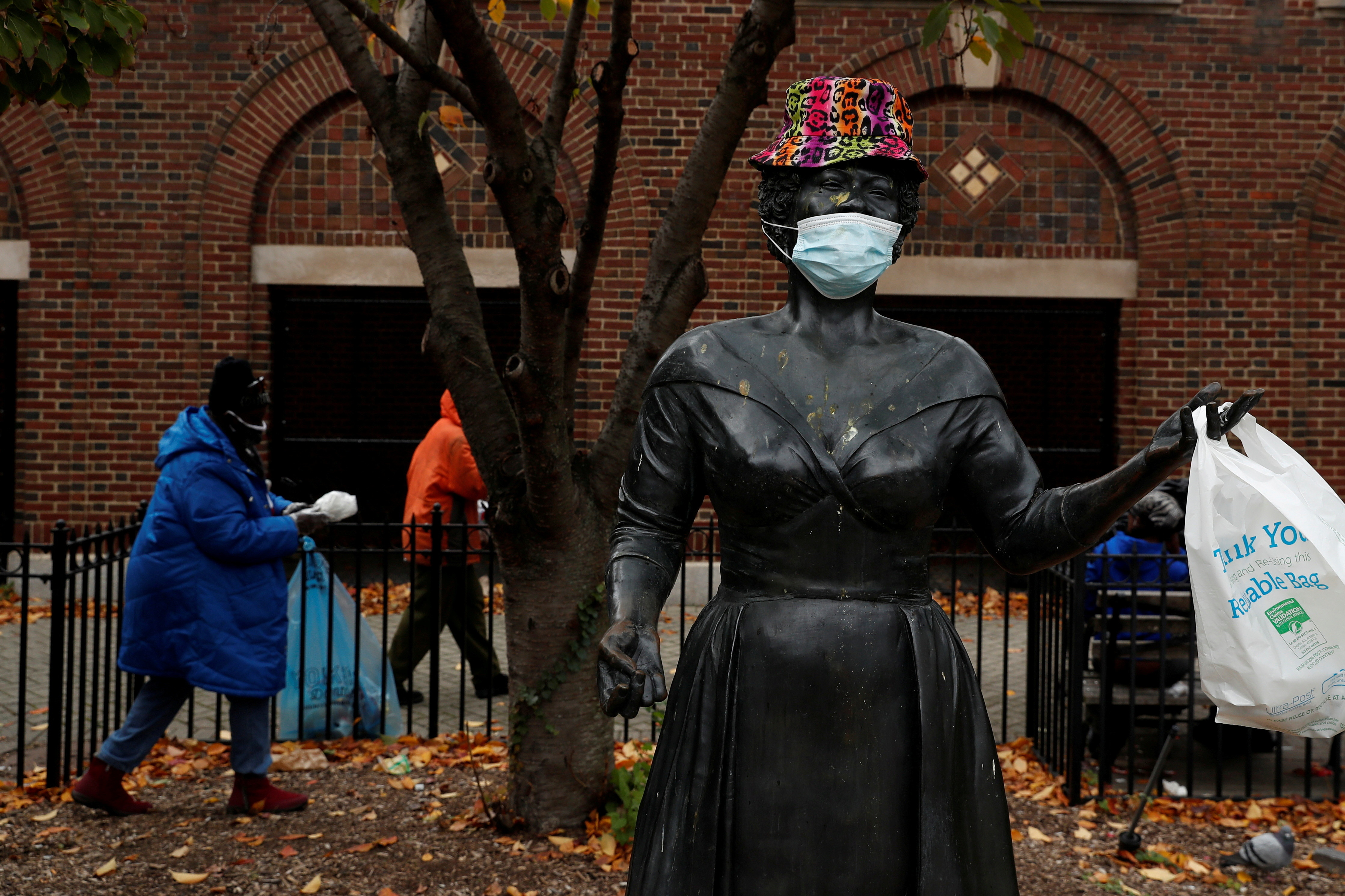 A bronze statue of late singer Ella Fitzgerald is seen wearing a hat and protective face mask, as the global outbreak of the coronavirus disease (COVID-19) continues, outside the Metro-North Railroad Station Plaza in Yonkers, New York, U.S., November 17, 2020. REUTERS/Shannon Stapleton     TPX IMAGES OF THE DAY - RC2B5K976NMW