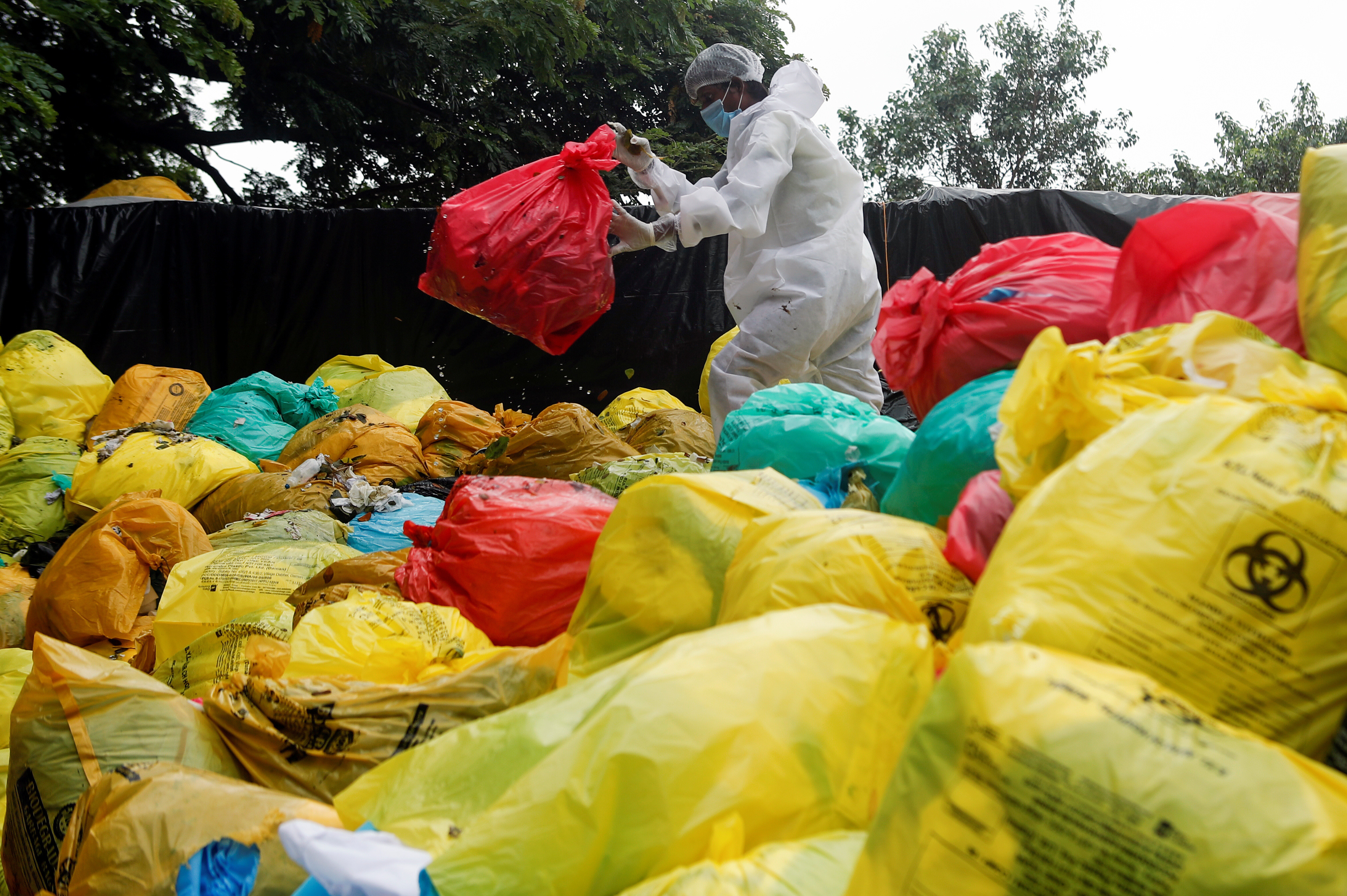 A man in personal protective equipment (PPE) clears bags filled with medical waste at a hospital, amidst the spread of the coronavirus disease.