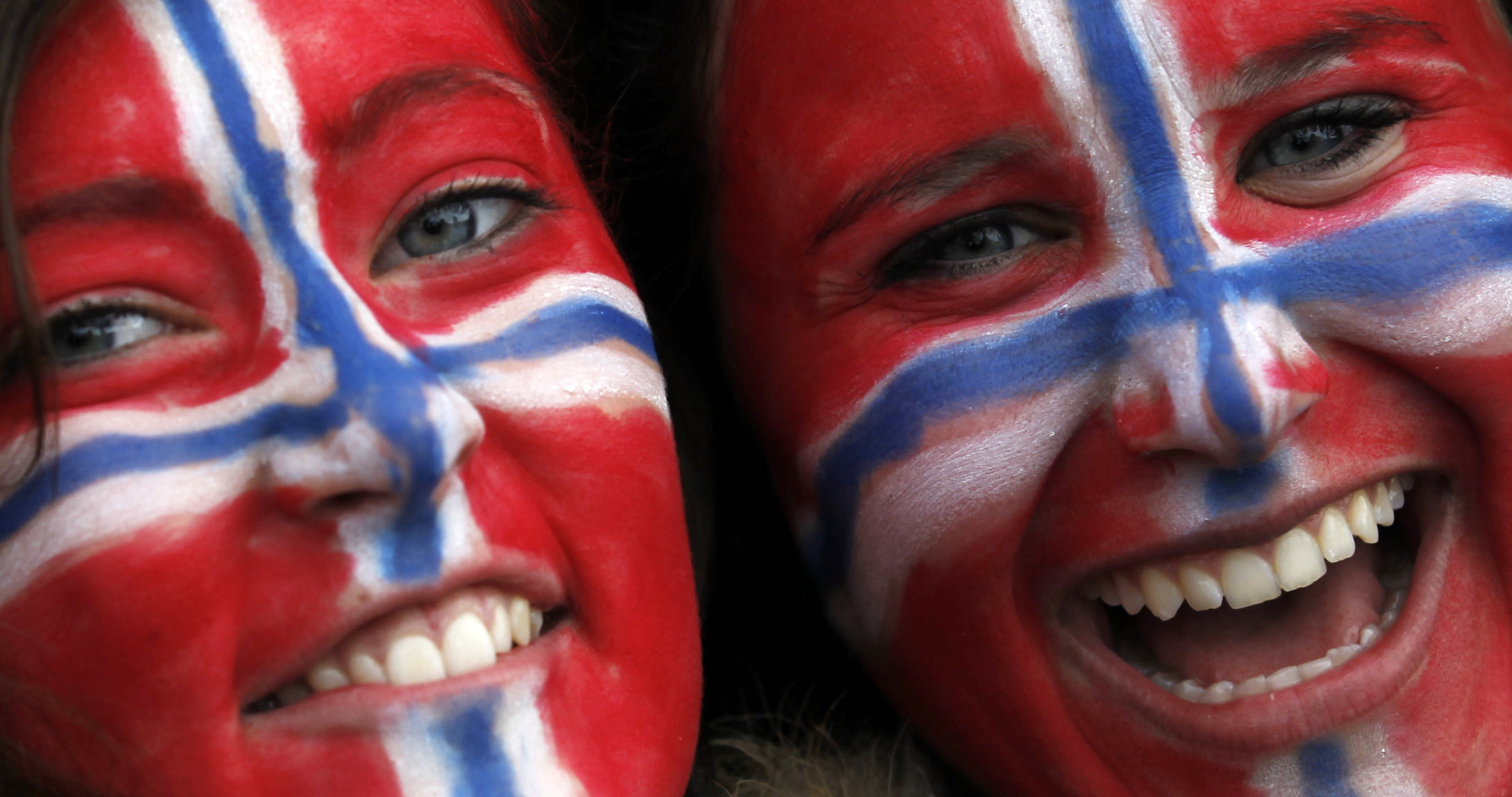 two women with the norwegian flag painted on their face smile for a photograph