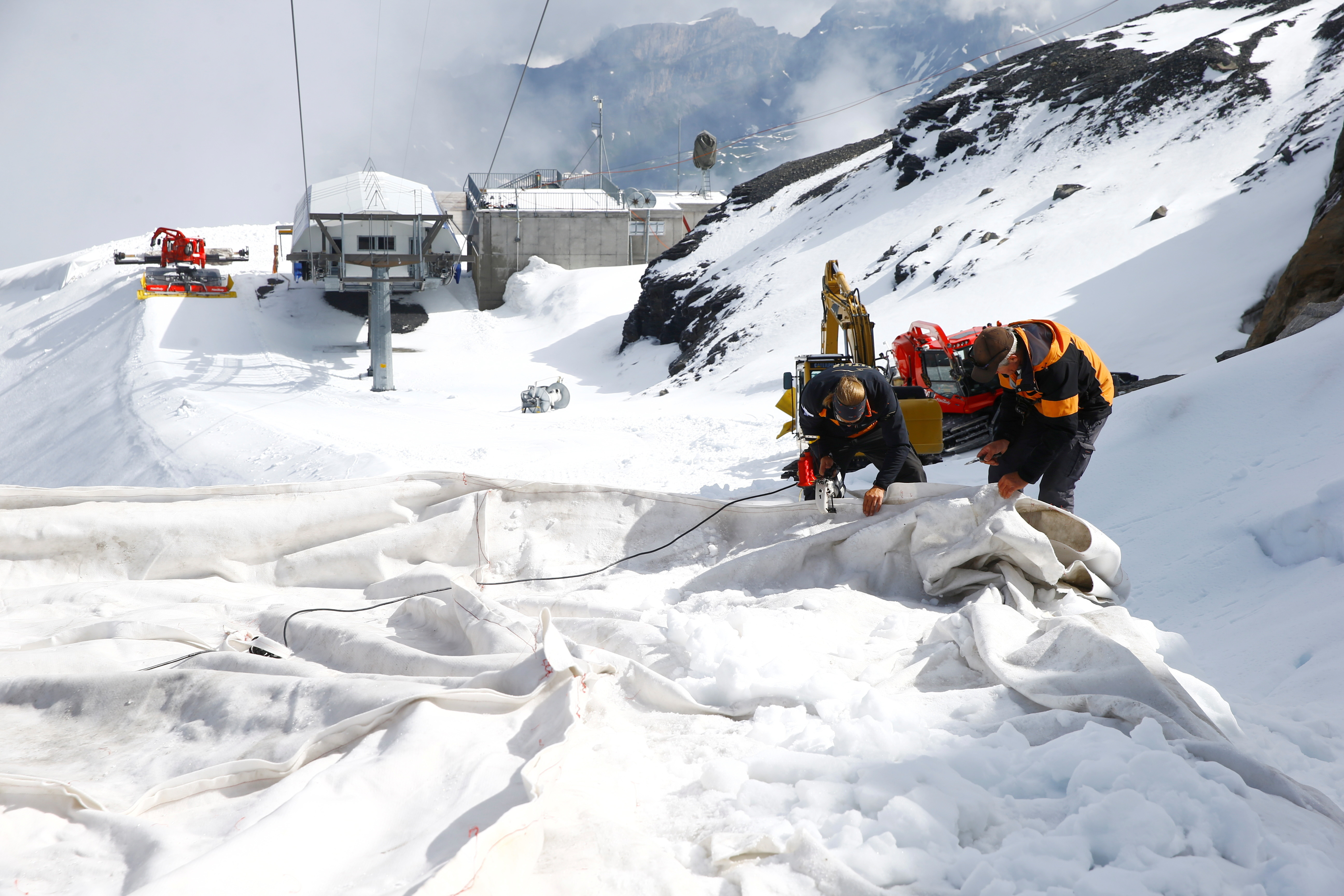 employees of Titlis Bergbahnen sew together blankets for the coverage of parts of the glacier to protect it against melting on Mount Titlis near the Alpine resort of Engelberg, Switzerland