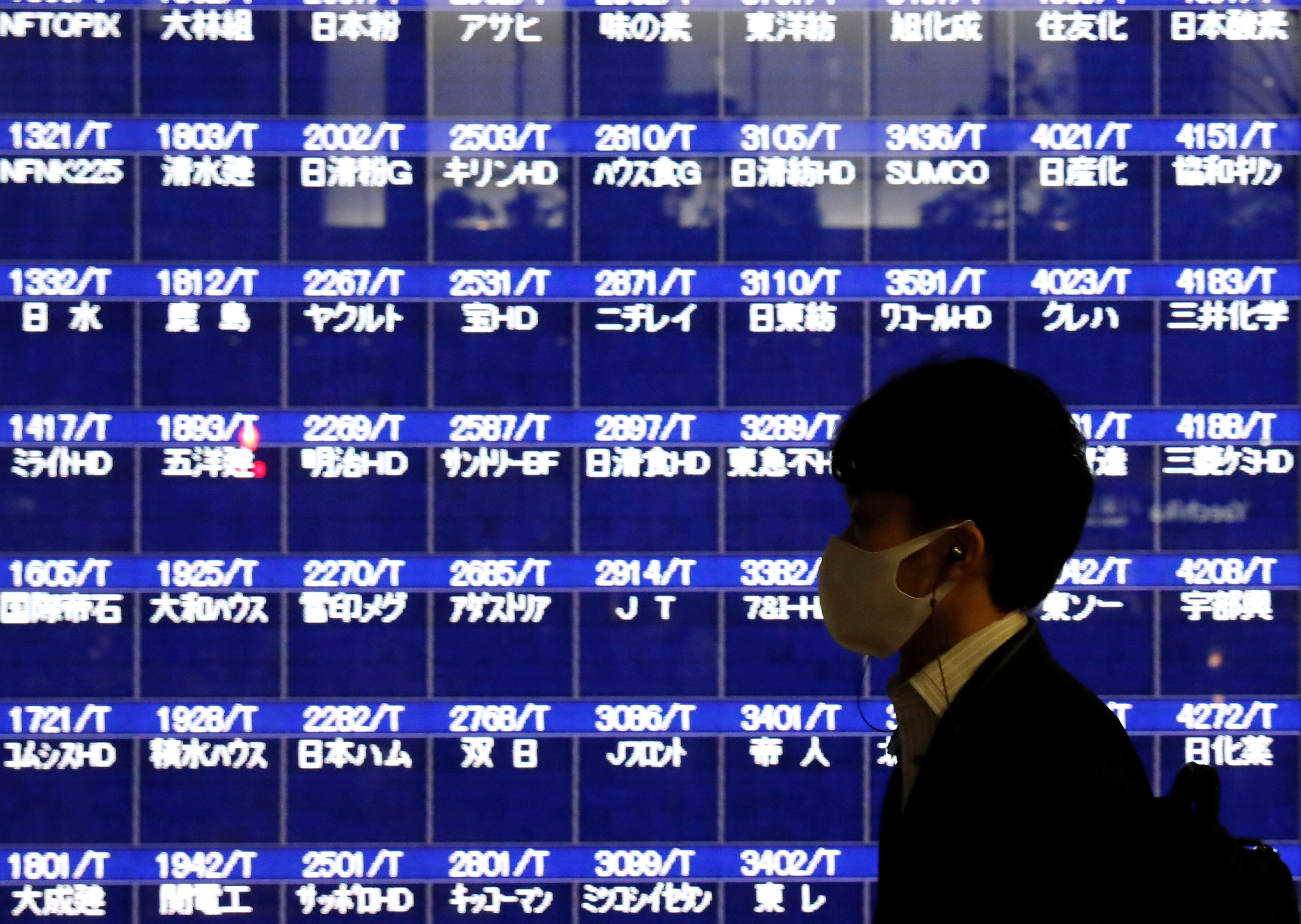 A passerby wearing a protective mask is silhouetted in front of a screen of blank prices on a stock quotation board after Tokyo Stock Exchange temporarily suspended all trading due to system problems, amid the coronavirus disease (COVID-19) pandemic, in Tokyo, Japan October 1, 2020.  REUTERS/Issei Kato - RC2M9J9BFFEH