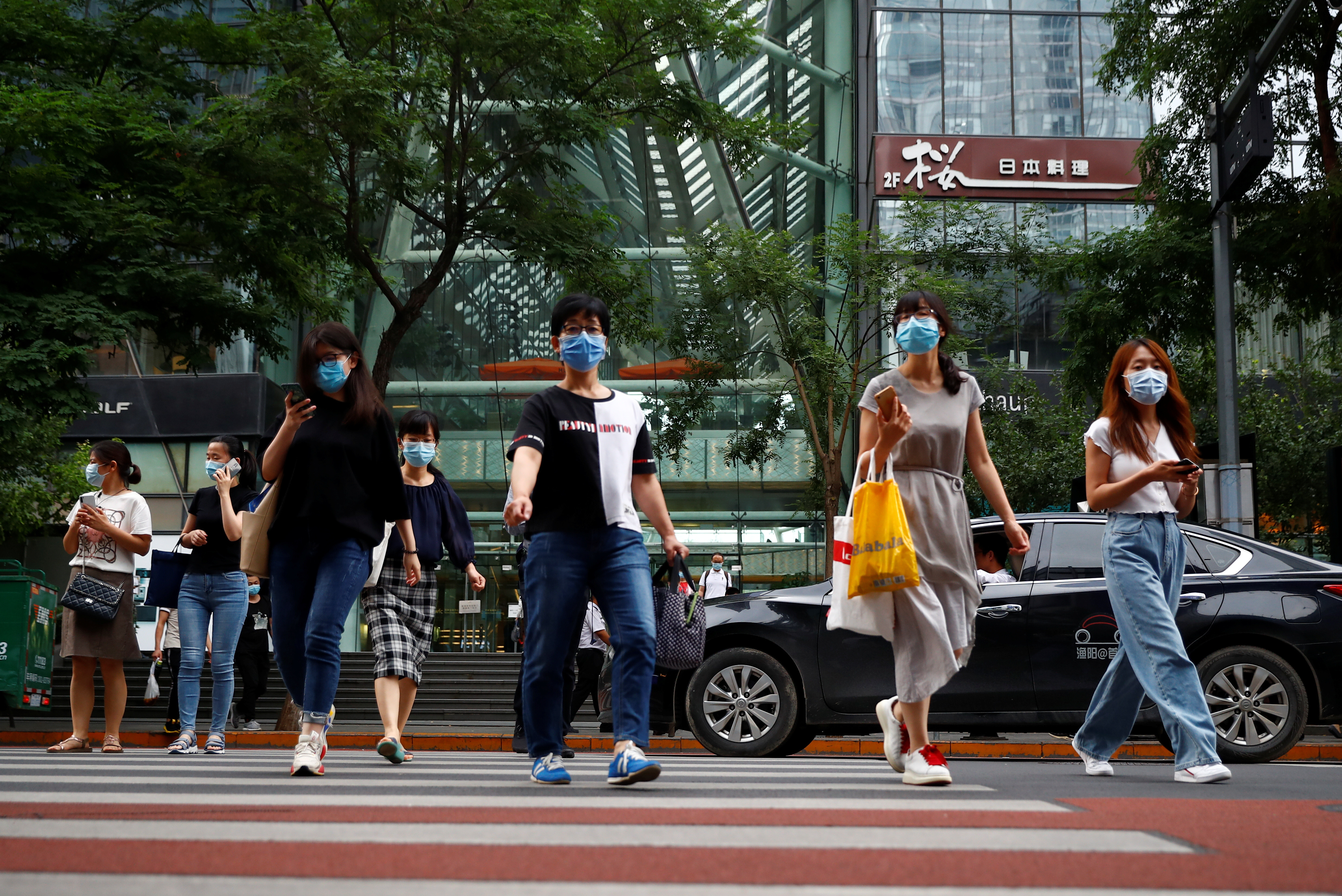 People wearing face masks leave an office building after work following a new outbreak of the coronavirus disease (COVID-19) in Beijing, China, June 29, 2020. REUTERS/Thomas Peter - RC2YIH9T7VOK