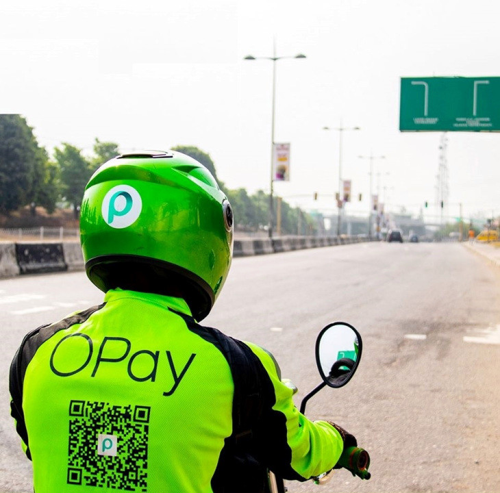 A person driving a motorbike in an OPay uniform