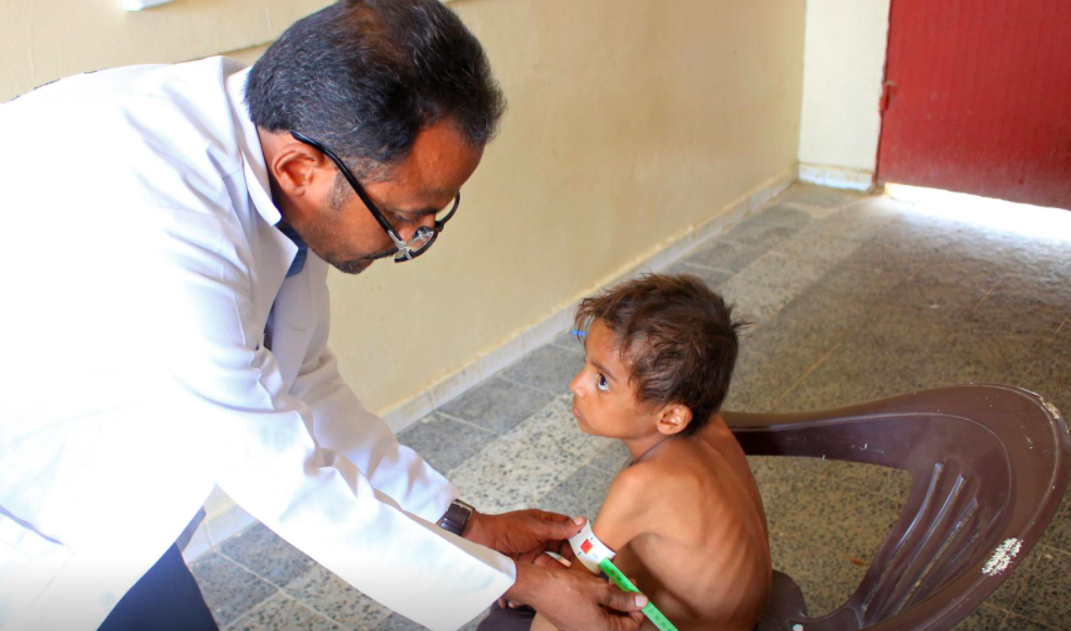 Hassan Merzam Muhammad pictured receiving medical attention by a doctor due to being severely malnourished.