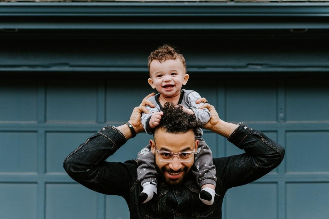 A man with his son on his shoulders.