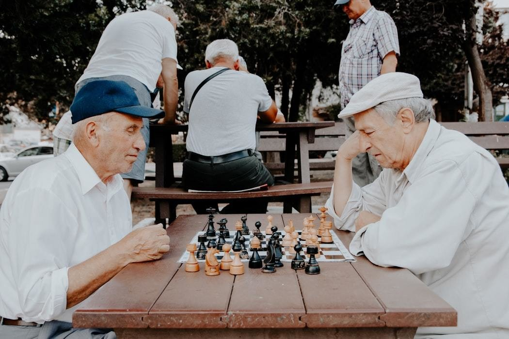 Two elderly gentlemen are playing chess in a park.