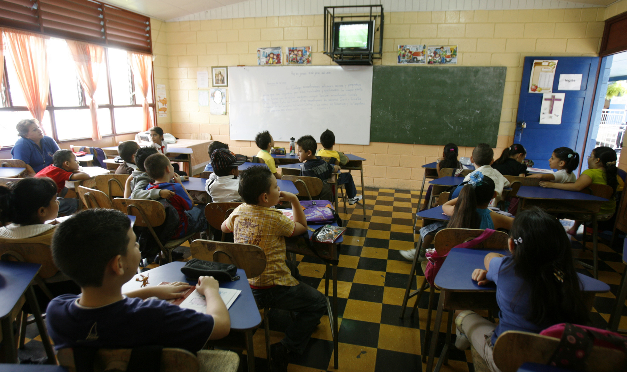 Schoolchildren are seen watching television, with their teachers, inside a school in Costa Rica.