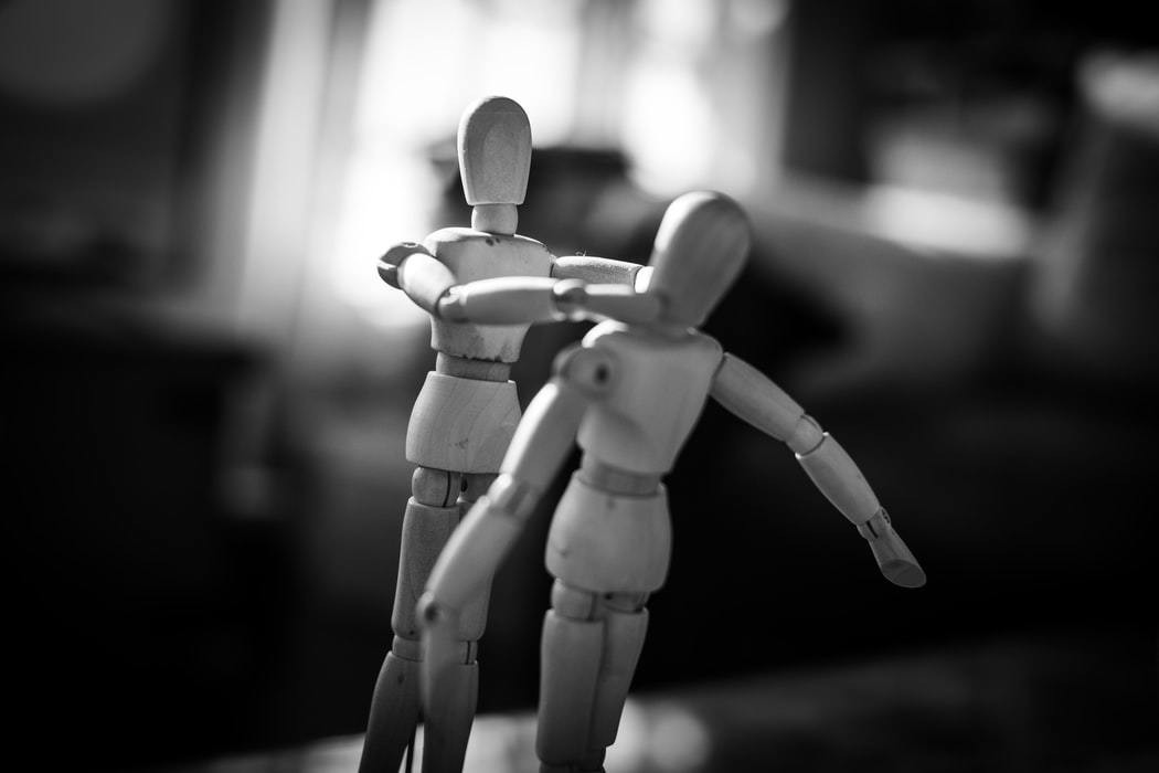 A picture of two stick figurines, one with its hands around the others neck, depicting a violent scene.