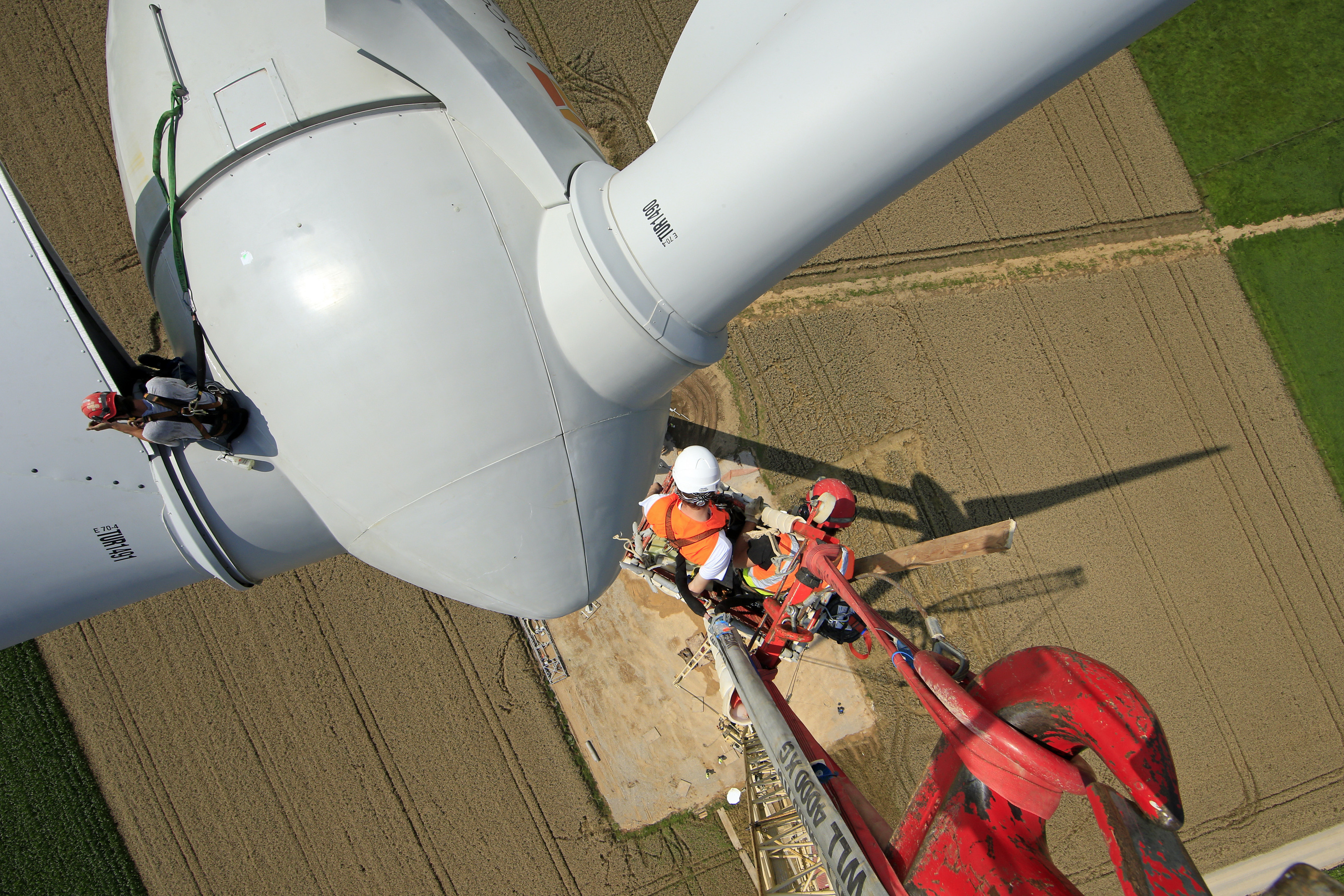 Employees work on a crane above an E-70 wind turbine manufactured by German company Enercon for La Compagnie du Vent (GDF SUEZ Group) during its installation at a wind farm in Meneslies, Picardie region, July 31, 2014. France announced in July a package of tax breaks and low-cost loans to improve insulation in buildings and boost investment in renewable energy, which is supposed to provide 40 percent of the country's electricity by 2030. Picture taken July  31, 2014.  REUTERS/Benoit Tessier   (FRANCE - Tags: ENERGY BUSINESS CONSTRUCTION ENVIRONMENT) - PM1EA841ETF01