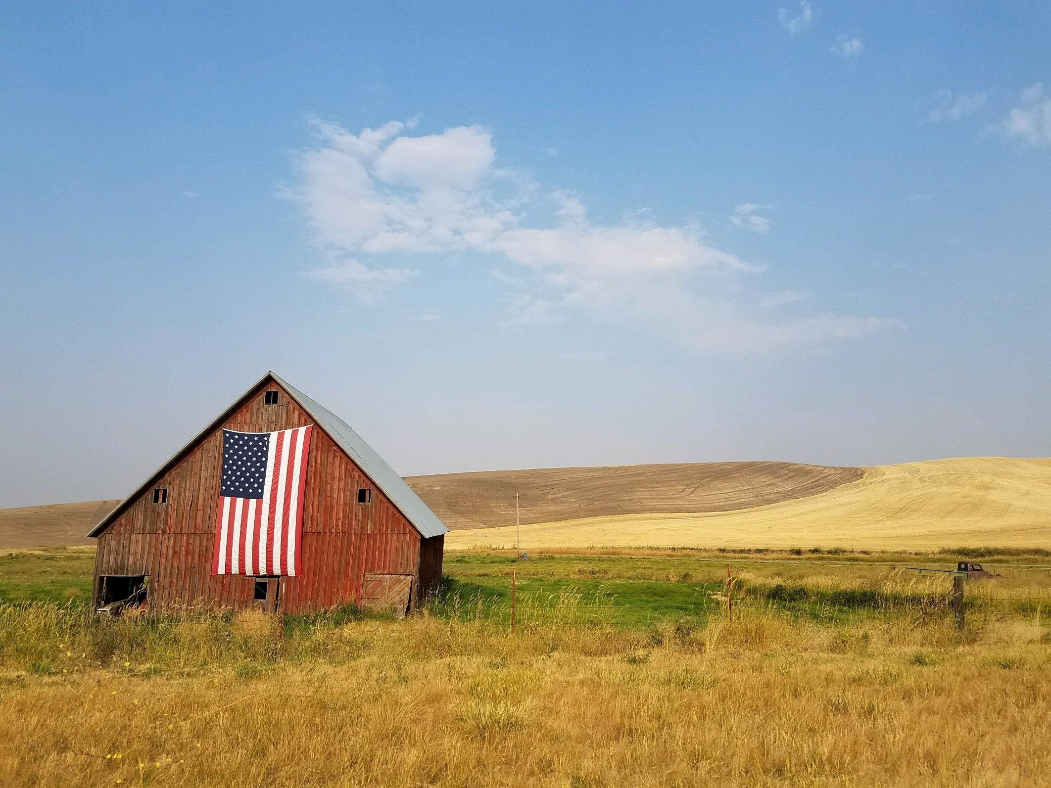 a barn with an american flag on the exterior, in a remote, agricultural landscape