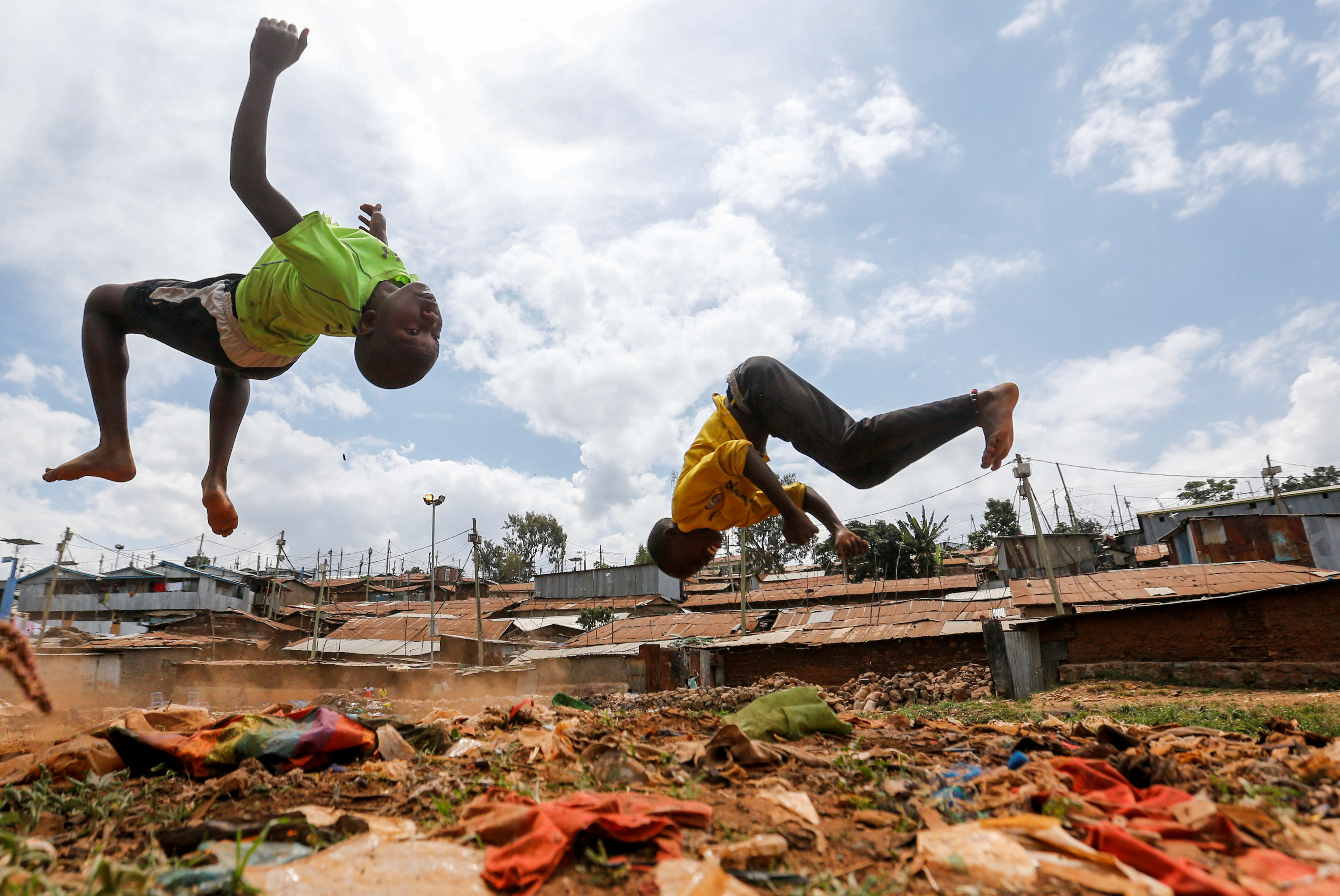 Children flip through the air as they play on dumped plastic materials amid the spread of the coronavirus disease (COVID-19) within Kibera slums in Nairobi, Kenya June 7, 2020. REUTERS/Thomas Mukoya     TPX IMAGES OF THE DAY - RC2E4H90JIZ3