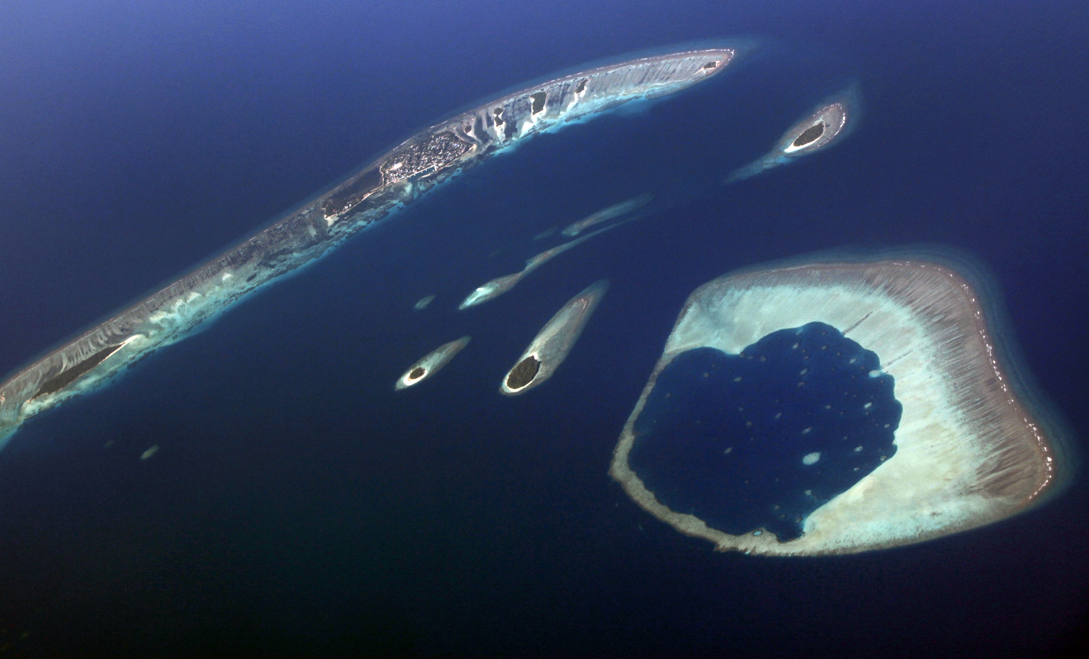 An aerial view shows an atoll in the Maldives December 9, 2009. Maldives has a population of some 400,000 islanders, whose livelihood from fishing and tourism is being hit by climate change. Maldives President Mohamed Nasheed said in November that 2 degrees Celsius warming would risk swamping the sand-rimmed coral atolls and islets, dotted with palm trees and mangrove clumps, that form his small country.REUTERS/Reinhard Krause (MALDIVES - Tags: POLITICS ENVIRONMENT TRAVEL) - GM1E5CE00F501