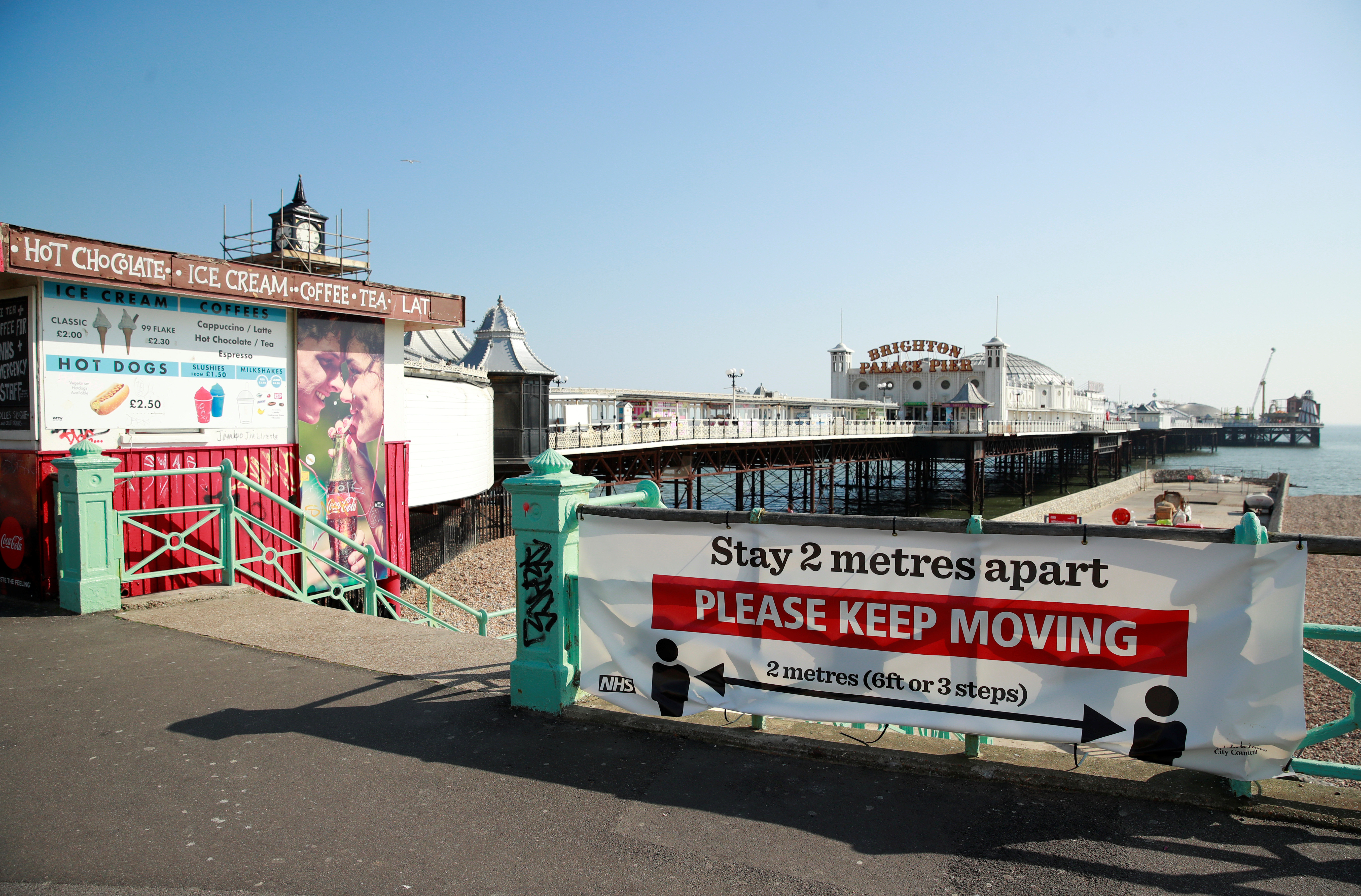 A sign telling people to stay 2 metres apart is seen on Brighton Palace Pier as the spread of the coronavirus disease (COVID-19) continues, Brighton, Britain, April 10, 2020. REUTERS/Andrew Couldridge - RC2Q1G96WCHO
