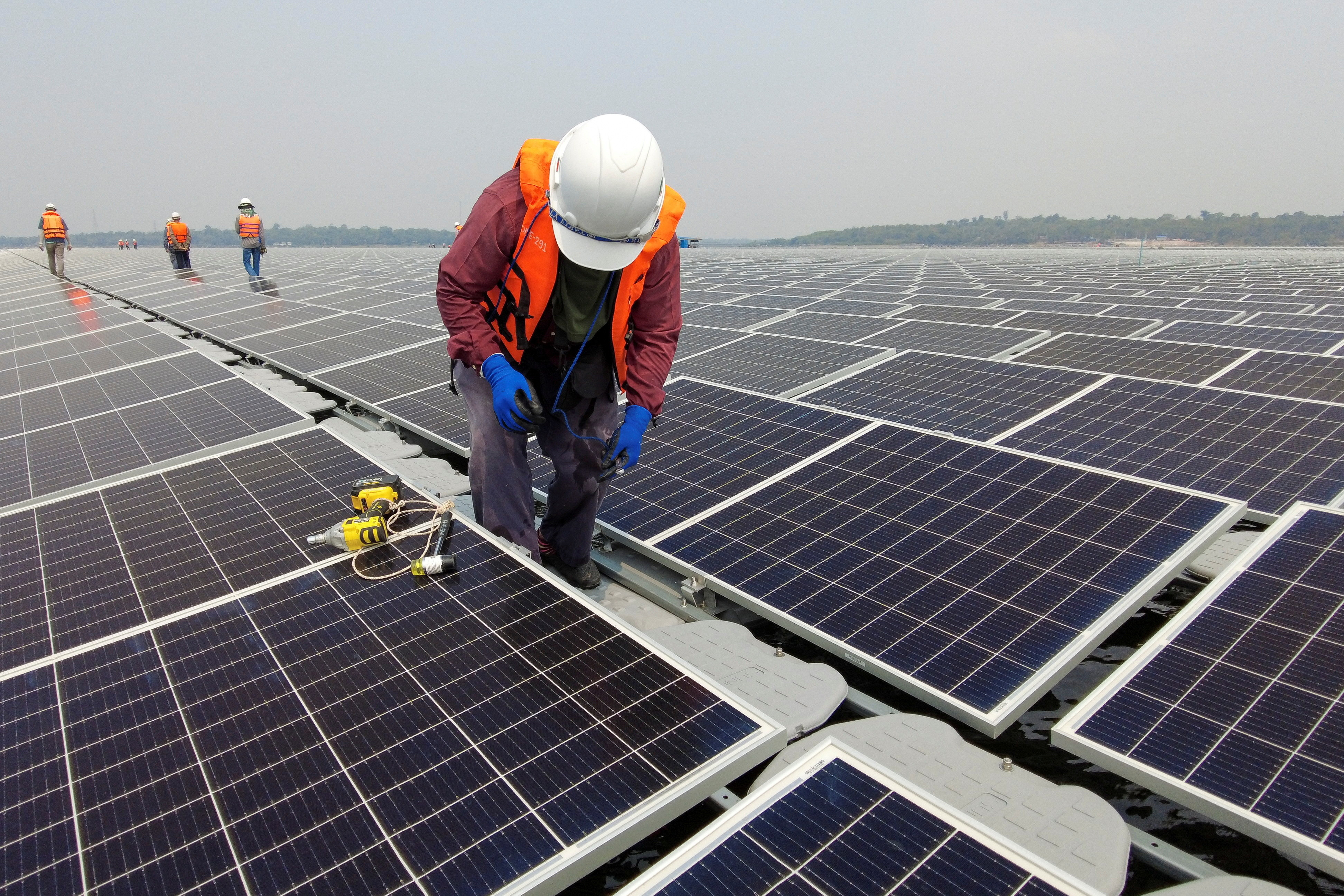 A worker stands between solar cell panels over the water surface of Sirindhorn Dam in Ubon Ratchathani, Thailand