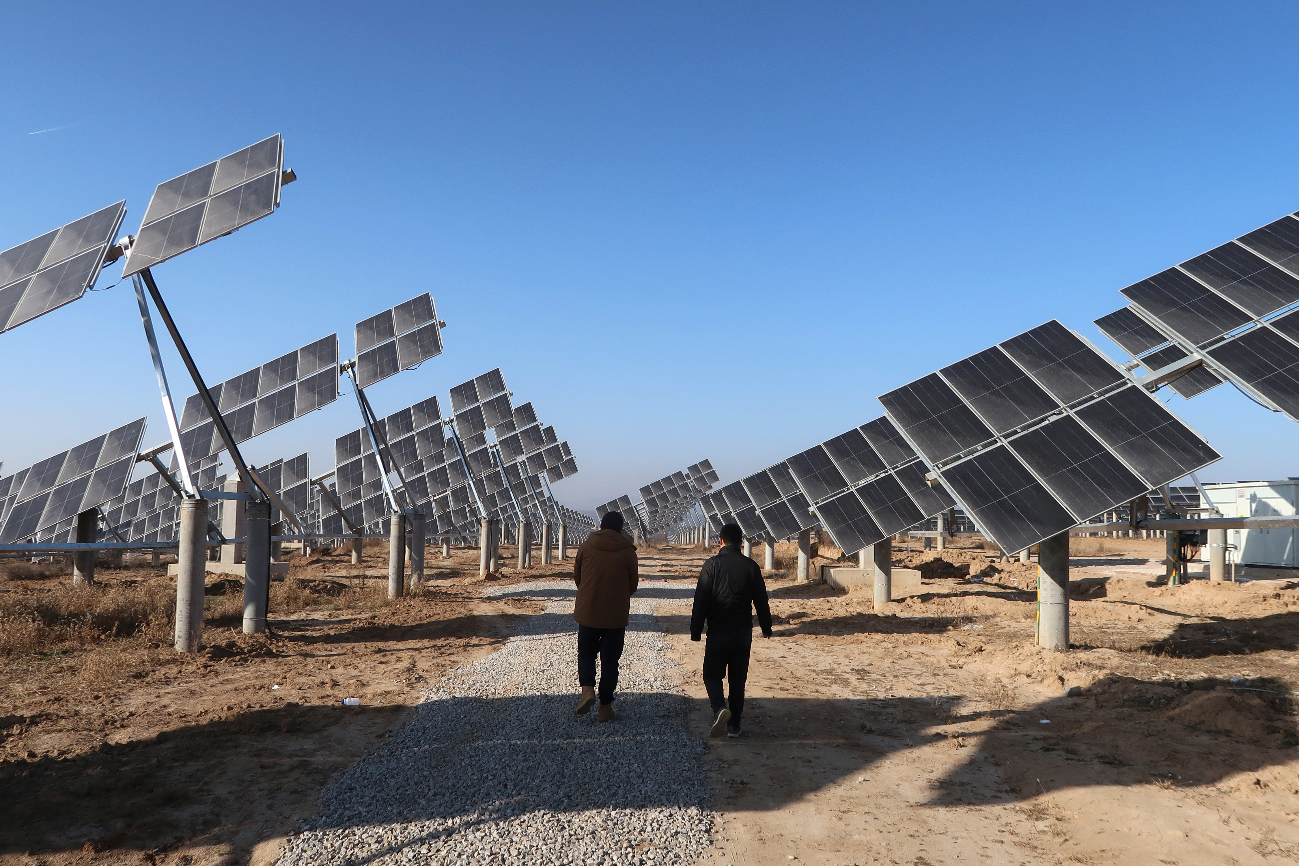 Workers walk at a solar power station in Tongchuan, Shaanxi province, China December 11, 2019. Picture taken December 11, 2019. REUTERS/Muyu Xu - RC2JXD9H0H3R