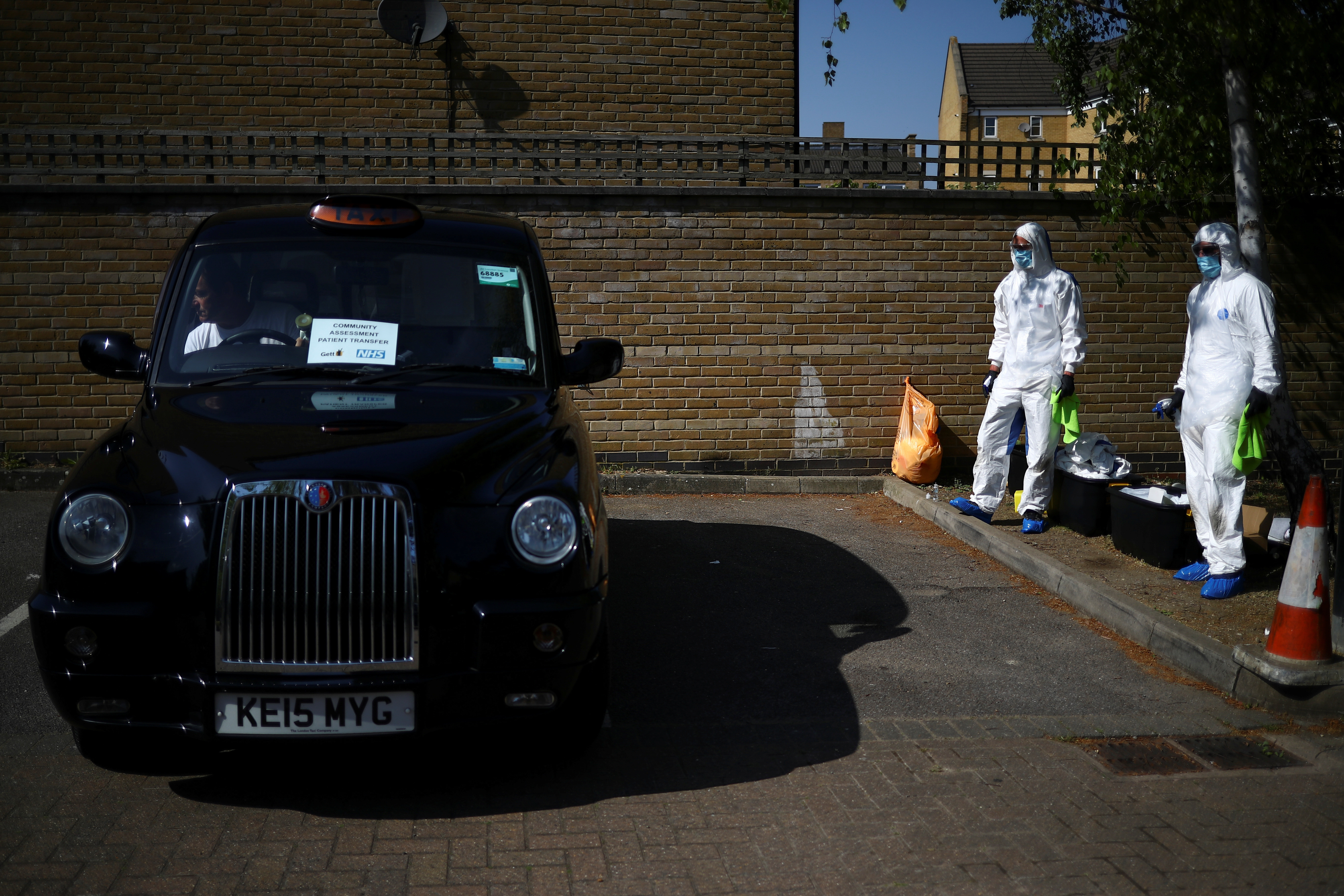 Workers from cleaning company Dropless wait to sanitise a London Black Cab as part of a service between taxi platform Gett and the NHS in south east London to ensure patients with COVID-19 symptoms can get to a local GP without using public transport as the spread of the coronavirus disease (COVID-19) continues, in London, Britain, April 23, 2020. REUTERS/Hannah Mckay - RC2FAG952KYV