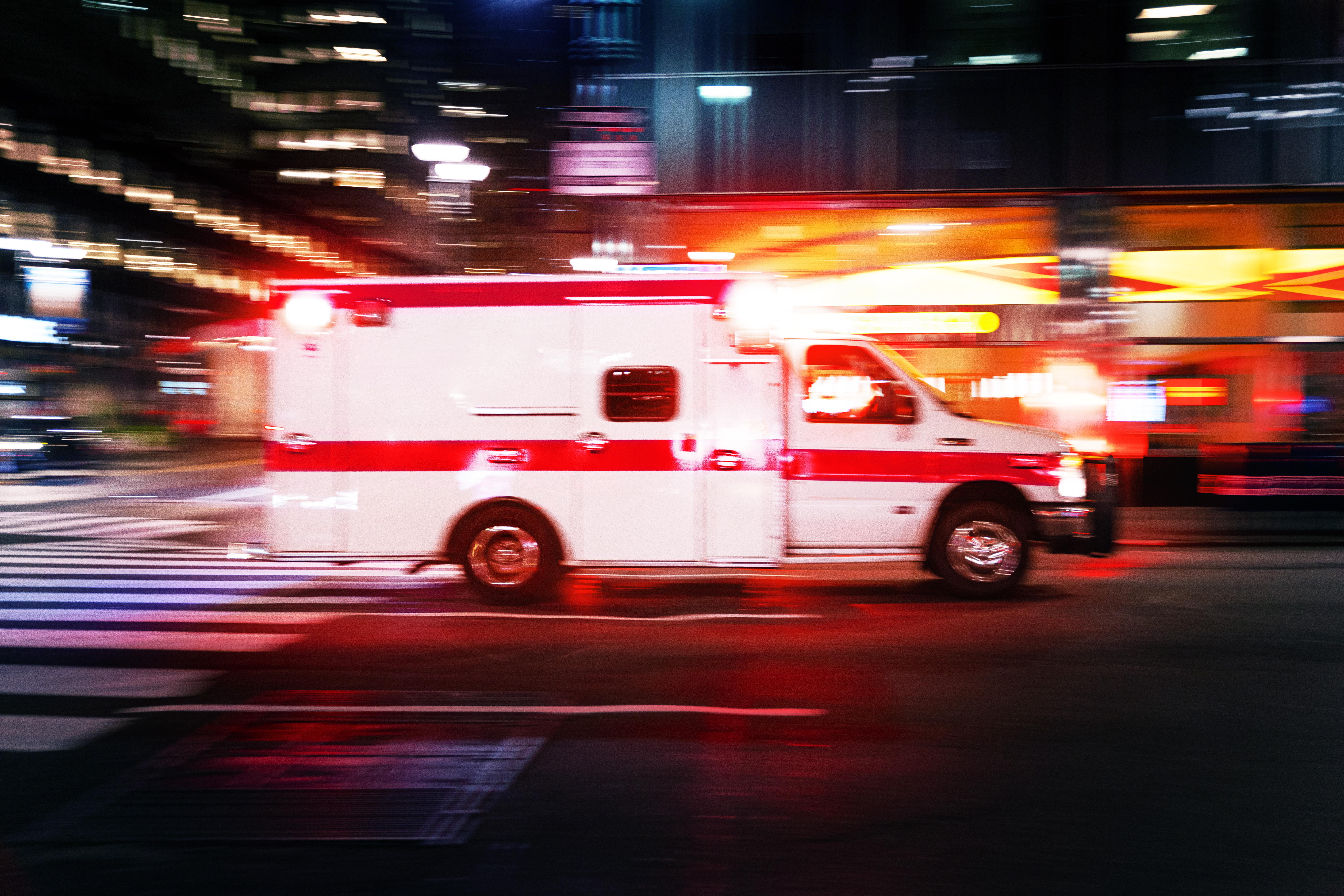 Ambulance speeding at night in New York City - motion blur panning action