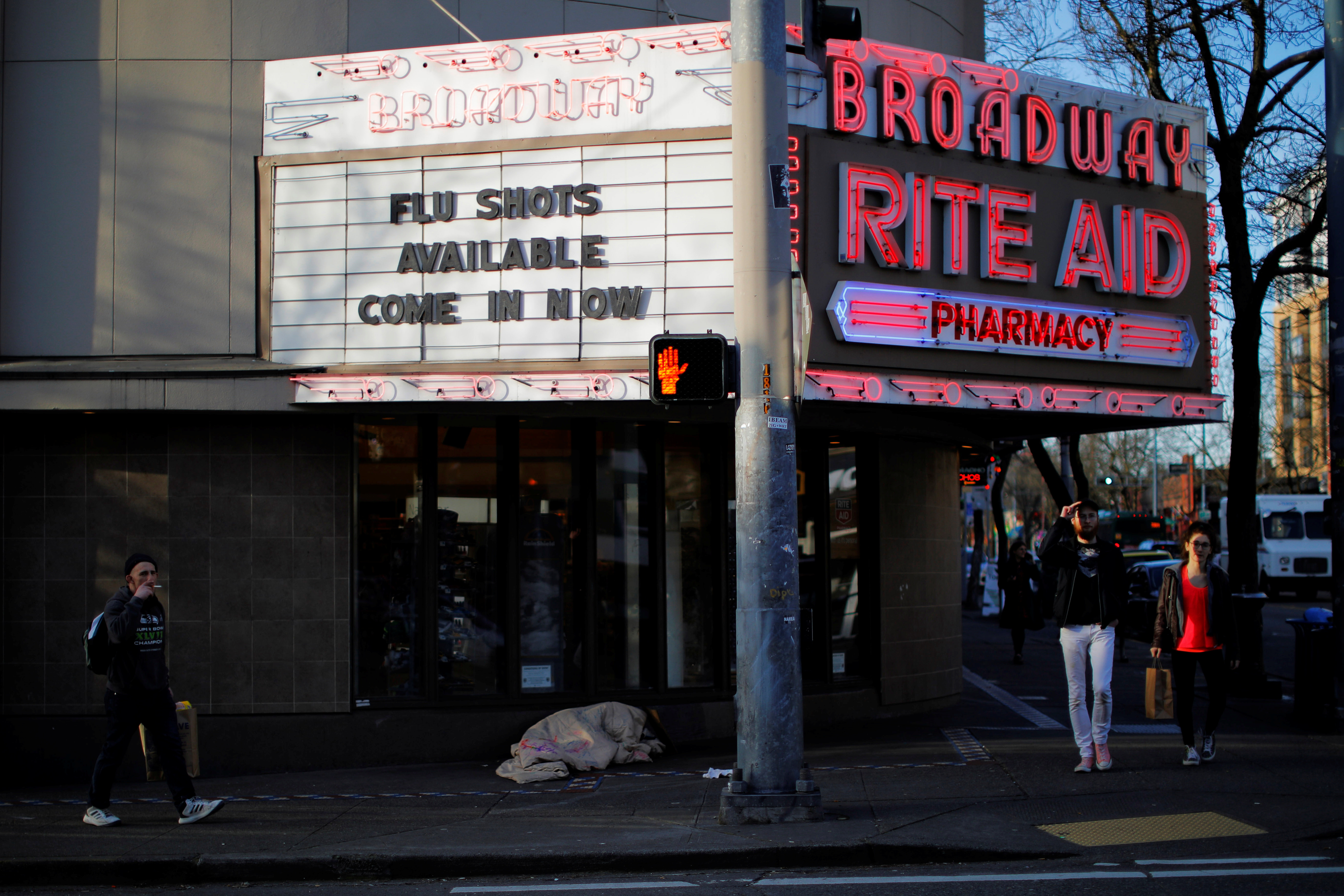 The sign over a drug store advertises flu shots amid the coronavirus (COVID-19) outbreak in Seattle, Washington, U.S., March 17, 2020.   REUTERS/Brian Snyder - RC24MF9UB0A3