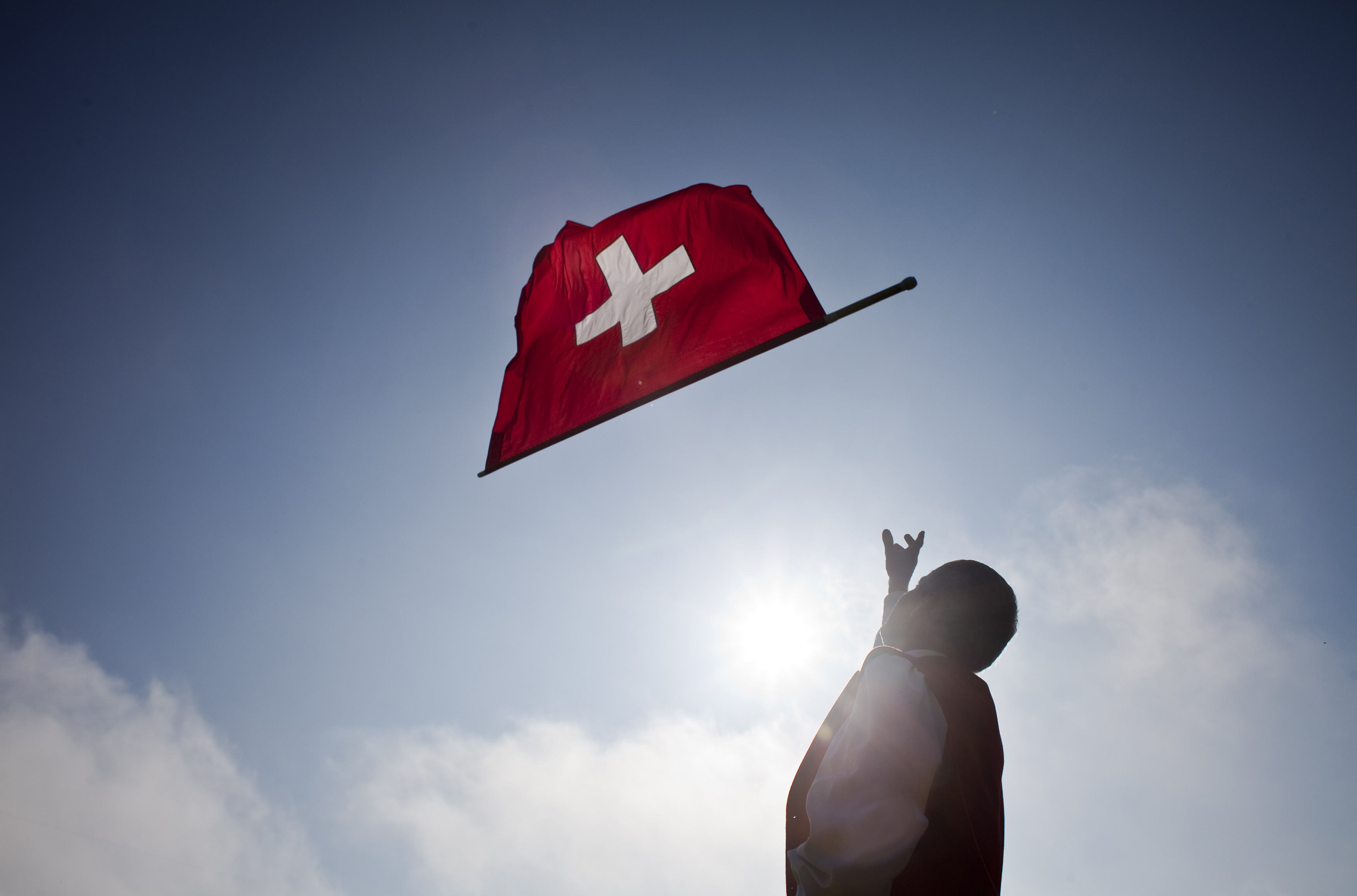 A man throws a Swiss national flag  in the air