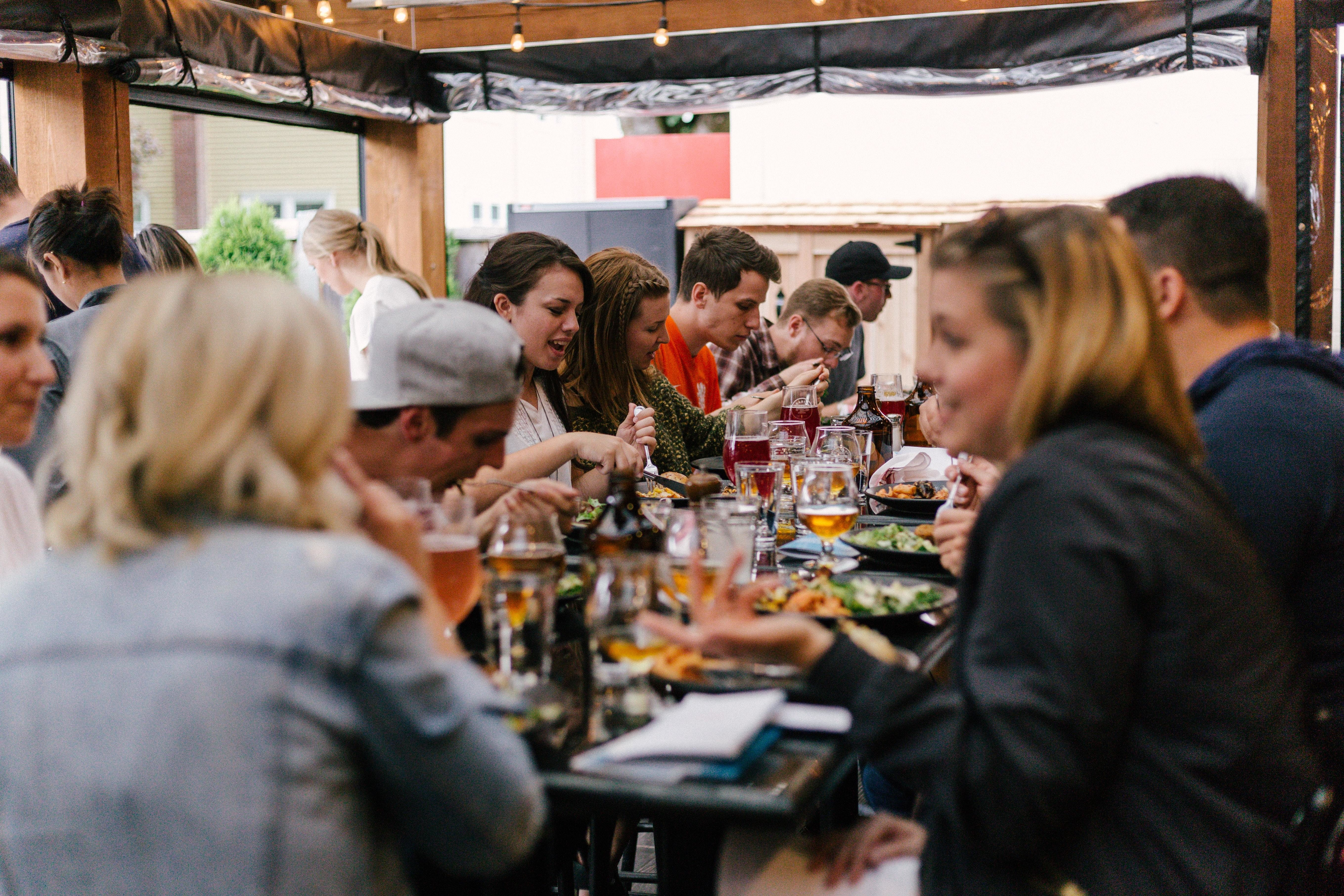 Americans are increasingly reporting a return to more normal activities, such as this social gathering over a meal