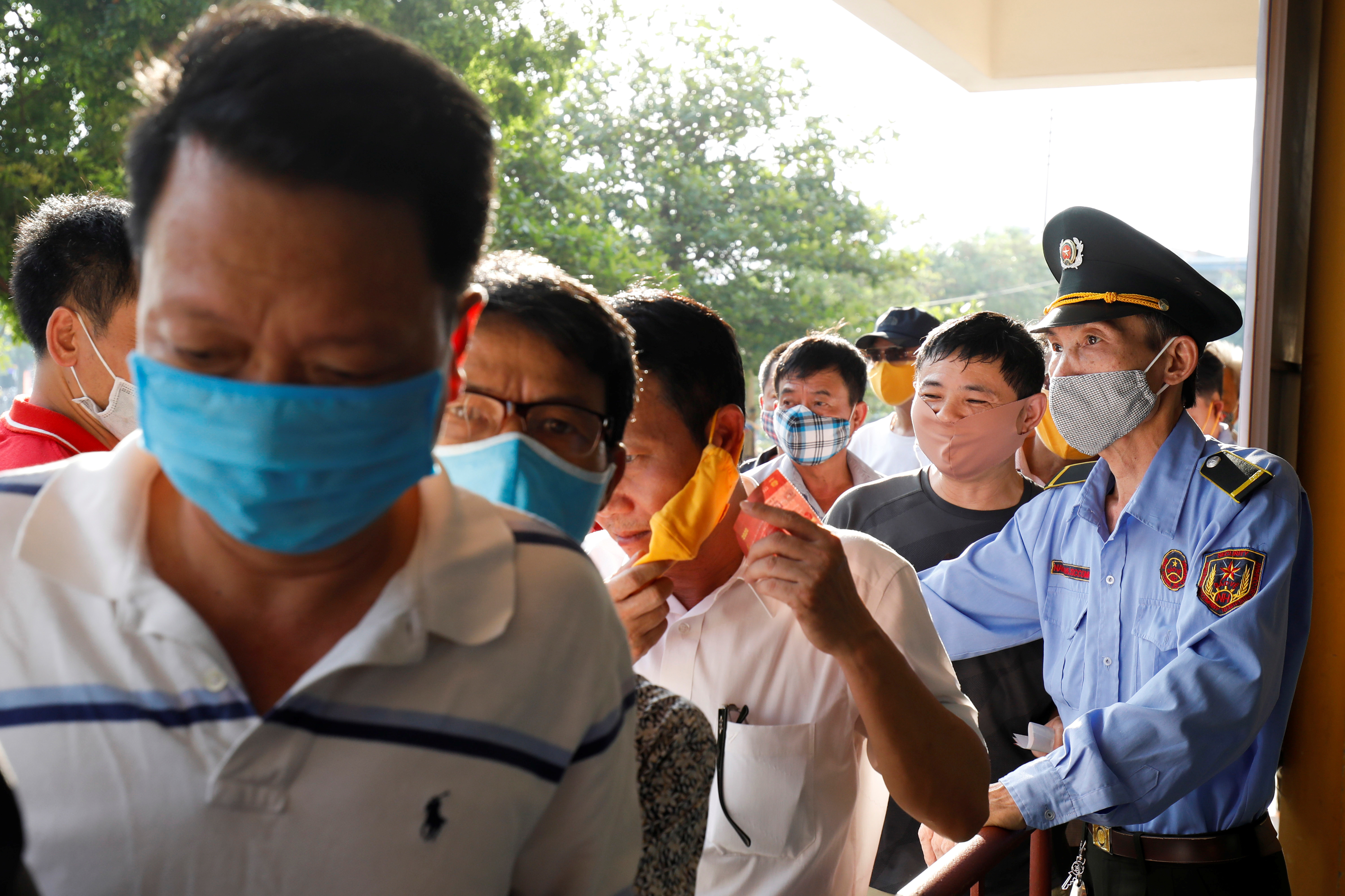 Soccer fans wearing protective masks arrive for a soccer match between Viettel and Duoc Nam Ha Nam Dinh of the V.League, the National soccer league, after the Government eased nationwide lockdown following the coronavirus disease (COVID-19) outbreak in Nam Dinh province, Vietnam June 5, 2020. REUTERS/Kham - RC223H97S5V8
