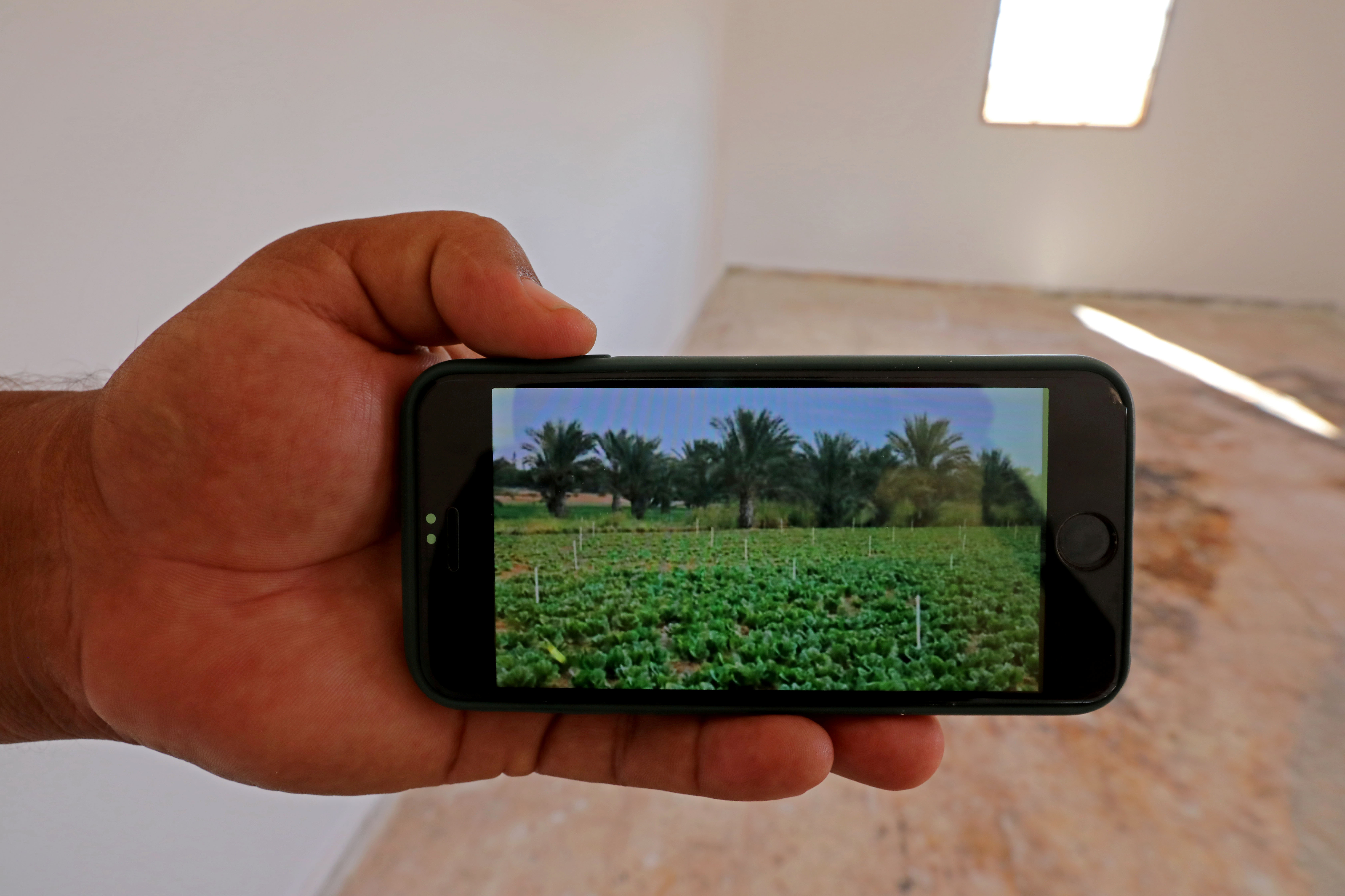 A member of Bouzid family shows a picture on his phone of of their farm, in Ain Zara, Tripoli, Libya, October 28, 2020. Picture taken October 28, 2020. REUTERS/Hazem Ahmed - RC2CSJ9VSCDX