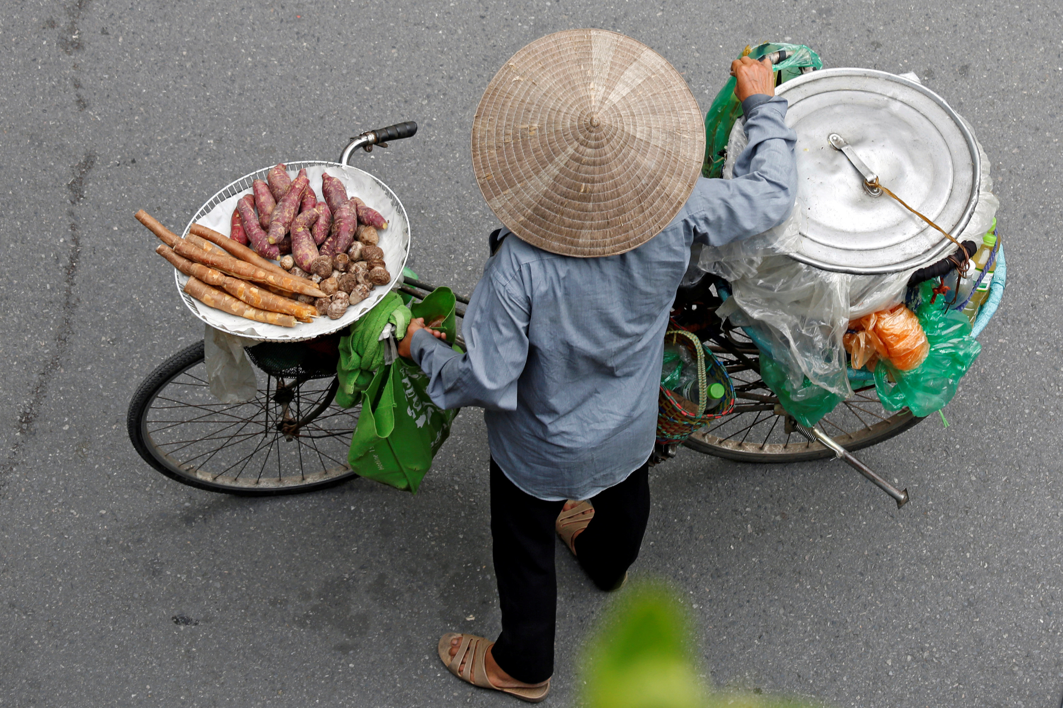 A Vietnamese woman transports cooked cassava and potato for sale by a bicycle on a street in Hanoi, Vietnam August 29, 2017. REUTERS/Kham - RC1ED76929E0