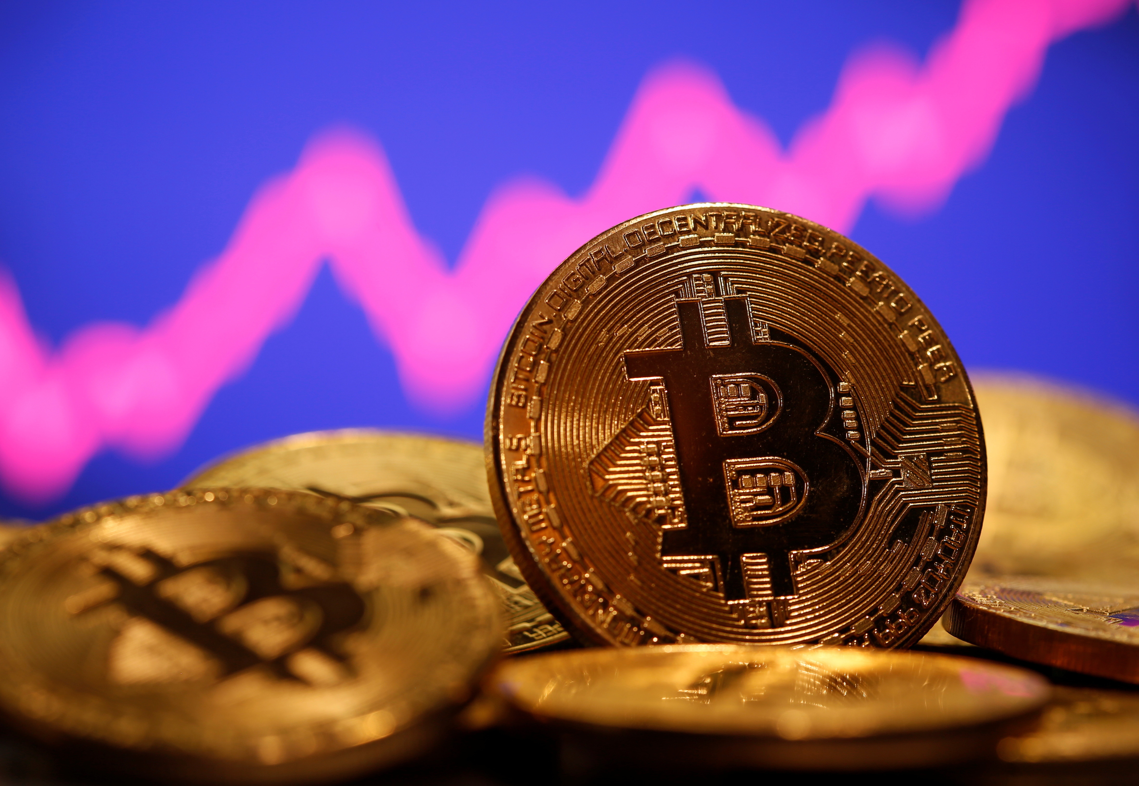 A representation of virtual currency Bitcoin is seen in front of a stock graph in this illustration taken January 8, 2021. REUTERS/Dado Ruvic - RC2R3L9VNVBH