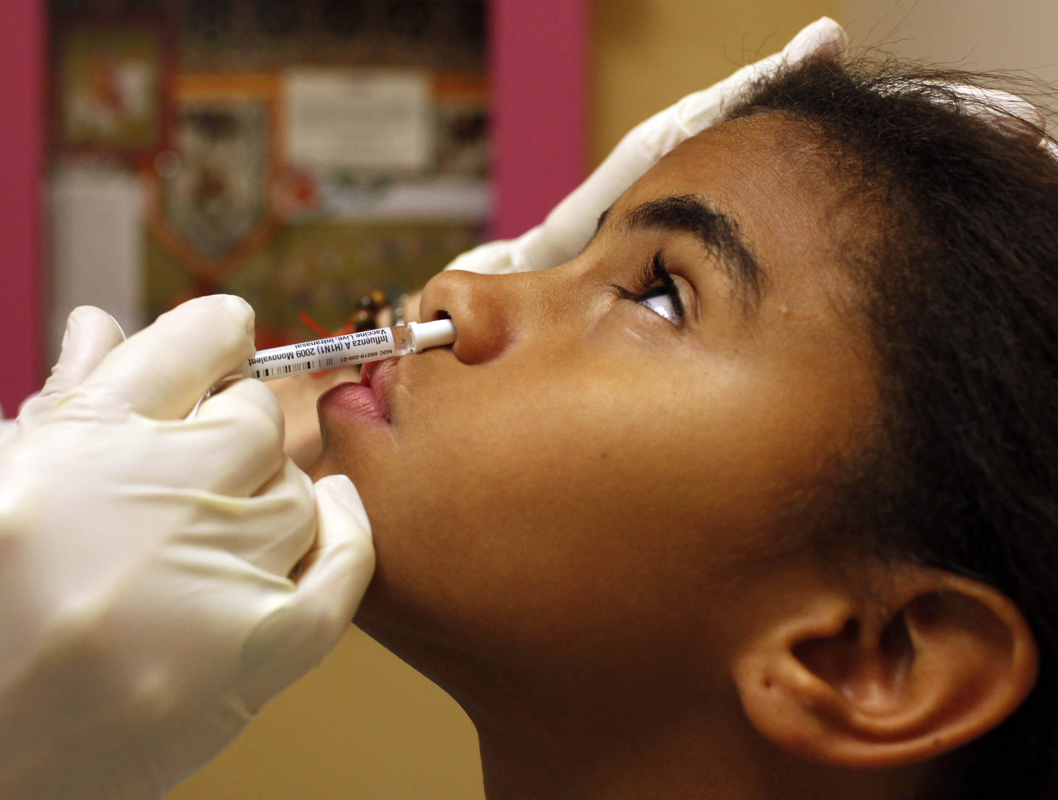 Eleven year-old Kerimal Suriel receives an H1N1 swine flu vaccine at the Children's Hospital Boston primary care clinic in Boston, Massachusetts October 7, 2009.   REUTERS/Brian Snyder    (UNITED STATES SCI TECH) - GM1E5A80H4C01
