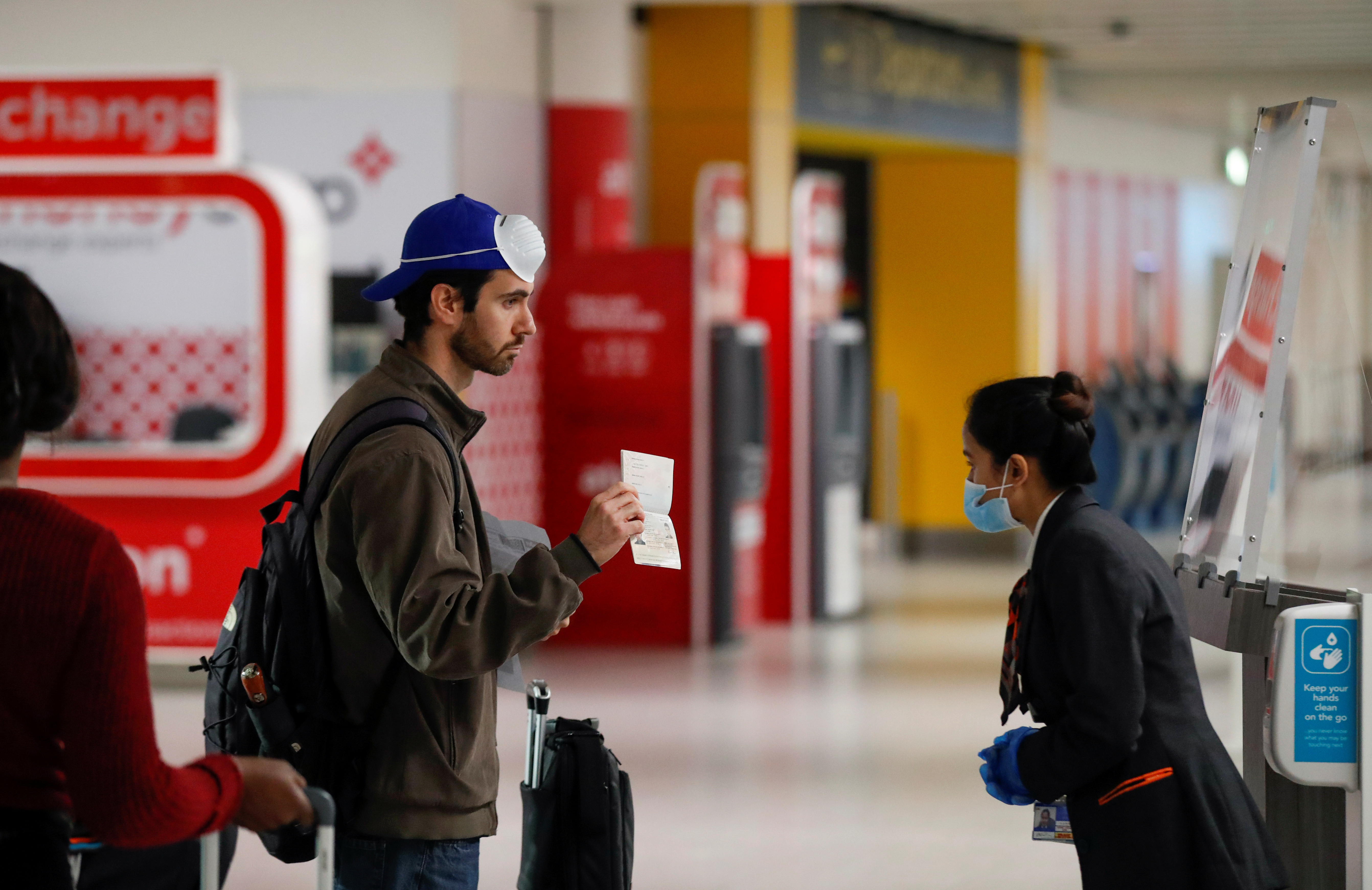 A passenger shows his passport to a staff member at Gatwick Airport, amid the coronavirus disease (COVID-19) outbreak, in Gatwick, Britain June 15, 2020.