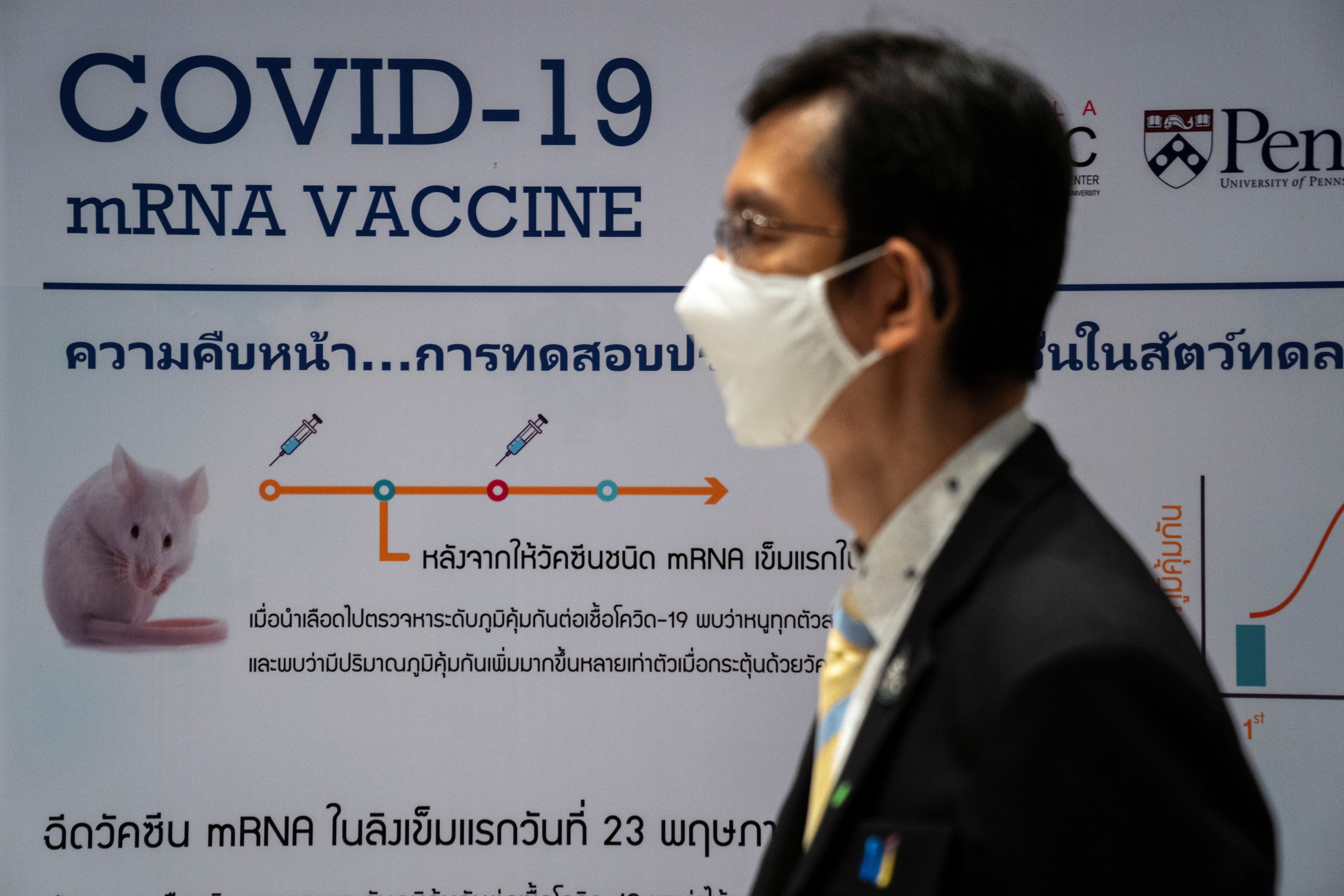 A man wearing a face mask stands next to a board showing the progress of developing an mRNA type vaccine candidate for the coronavirus disease (COVID-19) during a news conference at the National Primate Research Center of Chulalongkorn University in Saraburi province, Thailand, June 22, 2020. REUTERS/Athit Perawongmetha - RC29EH91GIEK