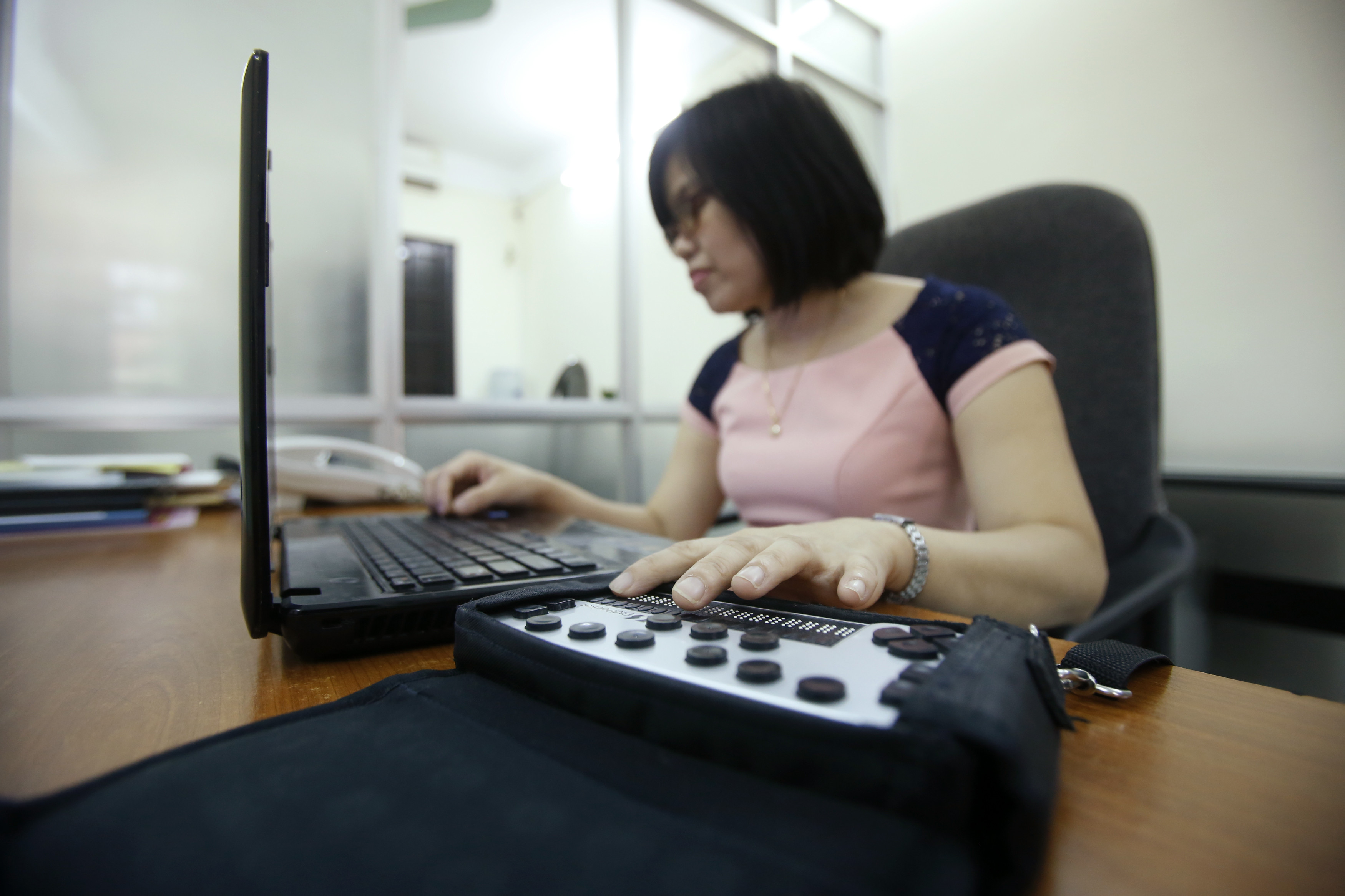 a woman who is blind, reads notes from a Braille notetaker as she works on her laptop