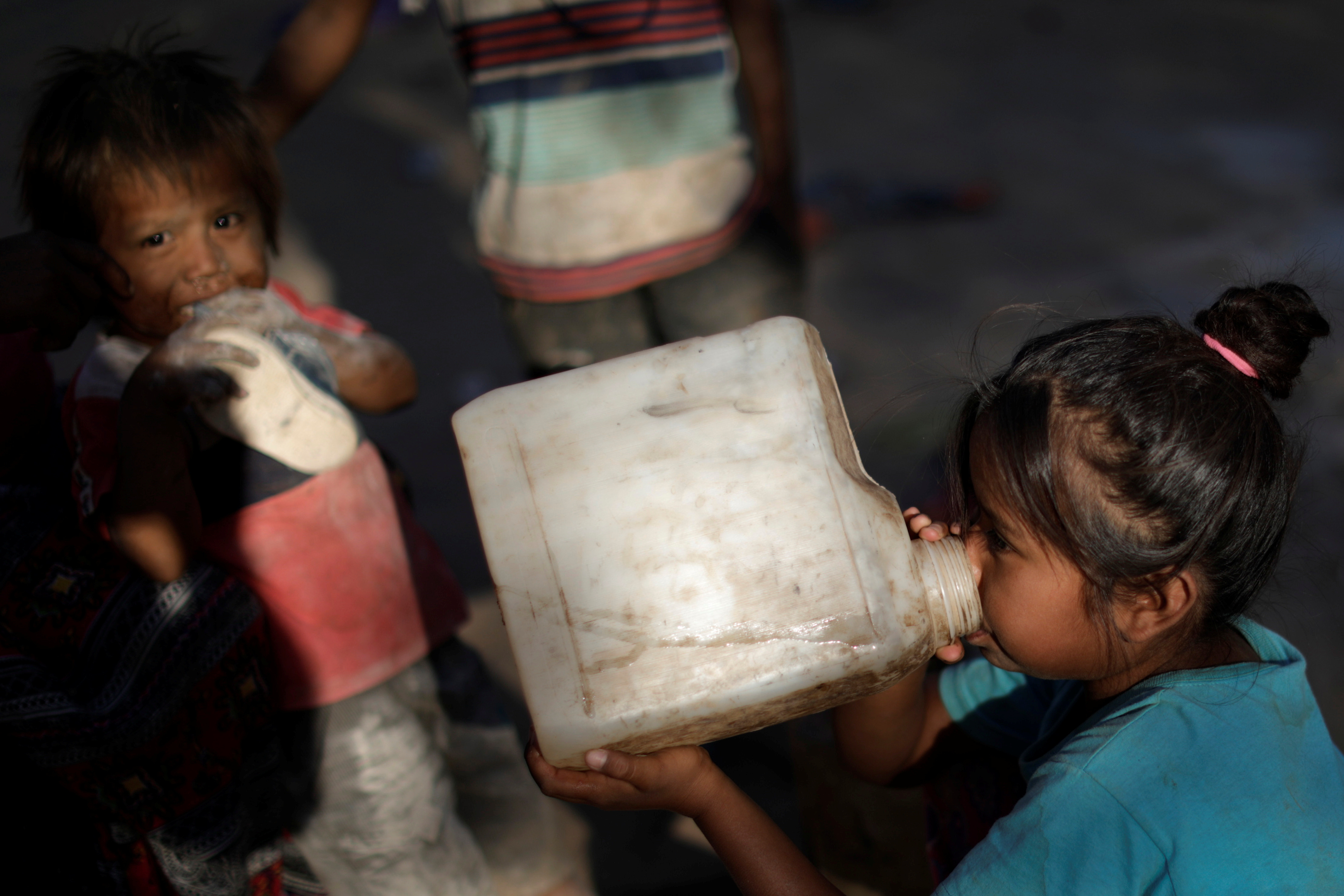 Children from the indigenous Wichi community drink water from plastic gallons, in the Salta province, Argentina, February 28, 2020. Picture taken February 28, 2020. REUTERS/Ueslei Marcelino - RC2ECF97W5DQ