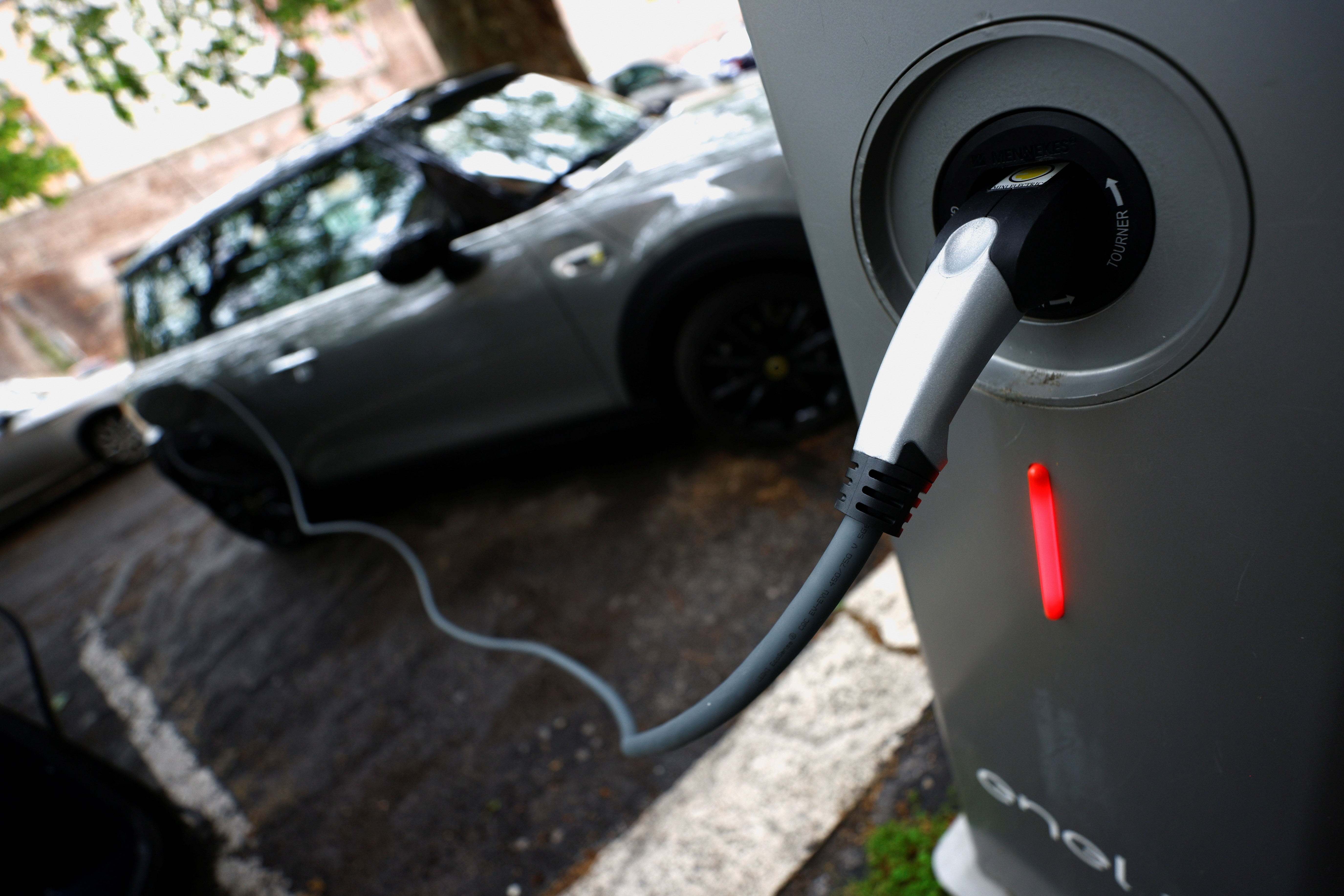 An electric car is seen plugged in at a charging point for electric vehicles
