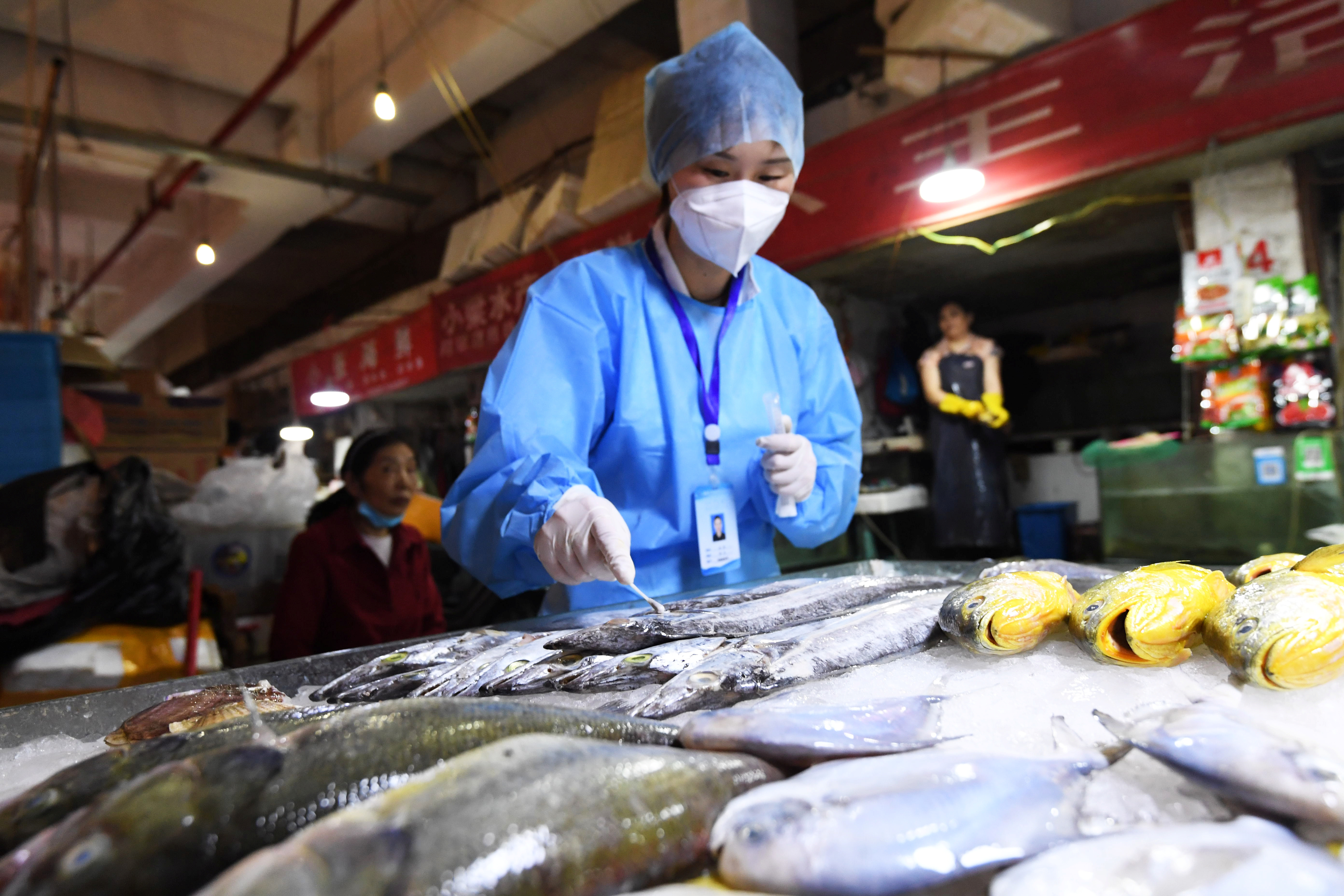 A staff member of Nanming district's Center for Disease Control and Prevention collects a swab from frozen fish for nucleic acid testing following the coronavirus disease (COVID-19) outbreak, at Wandong market in Guiyang, Guizhou province, China July 1, 2020. Picture taken July 1, 2020. cnsphoto via REUTERS   ATTENTION EDITORS - THIS IMAGE WAS PROVIDED BY A THIRD PARTY. CHINA OUT. - RC2HLH9NR80A