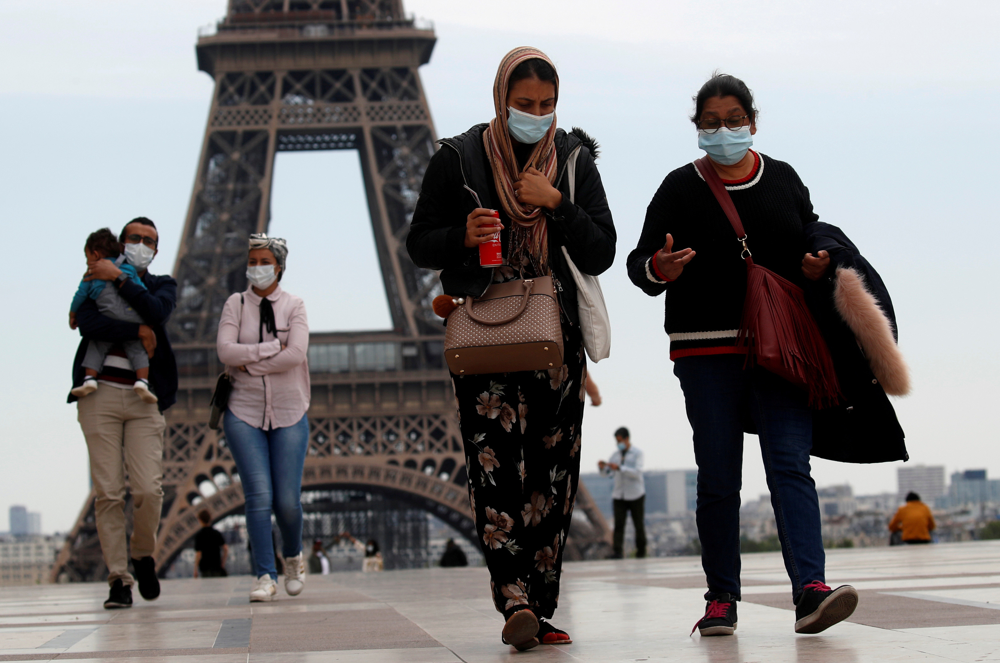People wearing face masks walk at Trocadero square near the Eiffel Tower, as France began a gradual end to a nationwide lockdown due to the coronavirus disease (COVID-19) in Paris, France, May 16, 2020. REUTERS/Gonzalo Fuentes     TPX IMAGES OF THE DAY - RC2OPG9EW4WV
