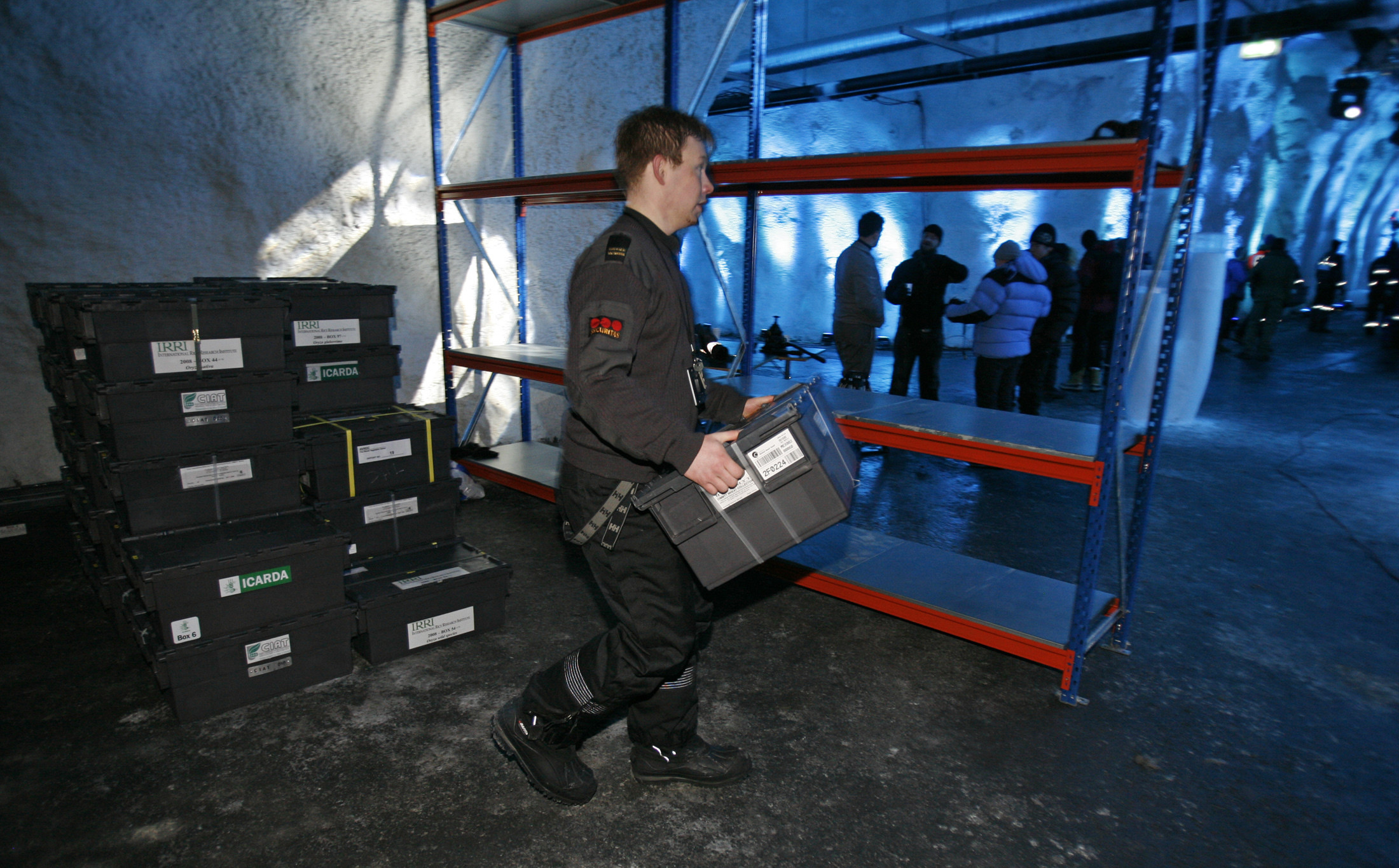 A worker carries a box of seeds into the main storage room during the opening ceremony of the Global Seed Vault in Longyearbyen February 26, 2008.   REUTERS/Bob Strong (NORWAY) - GM1E42Q1JY101