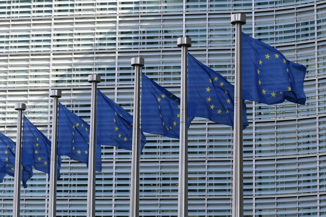 Seven European Union flags are seen in front of a building.