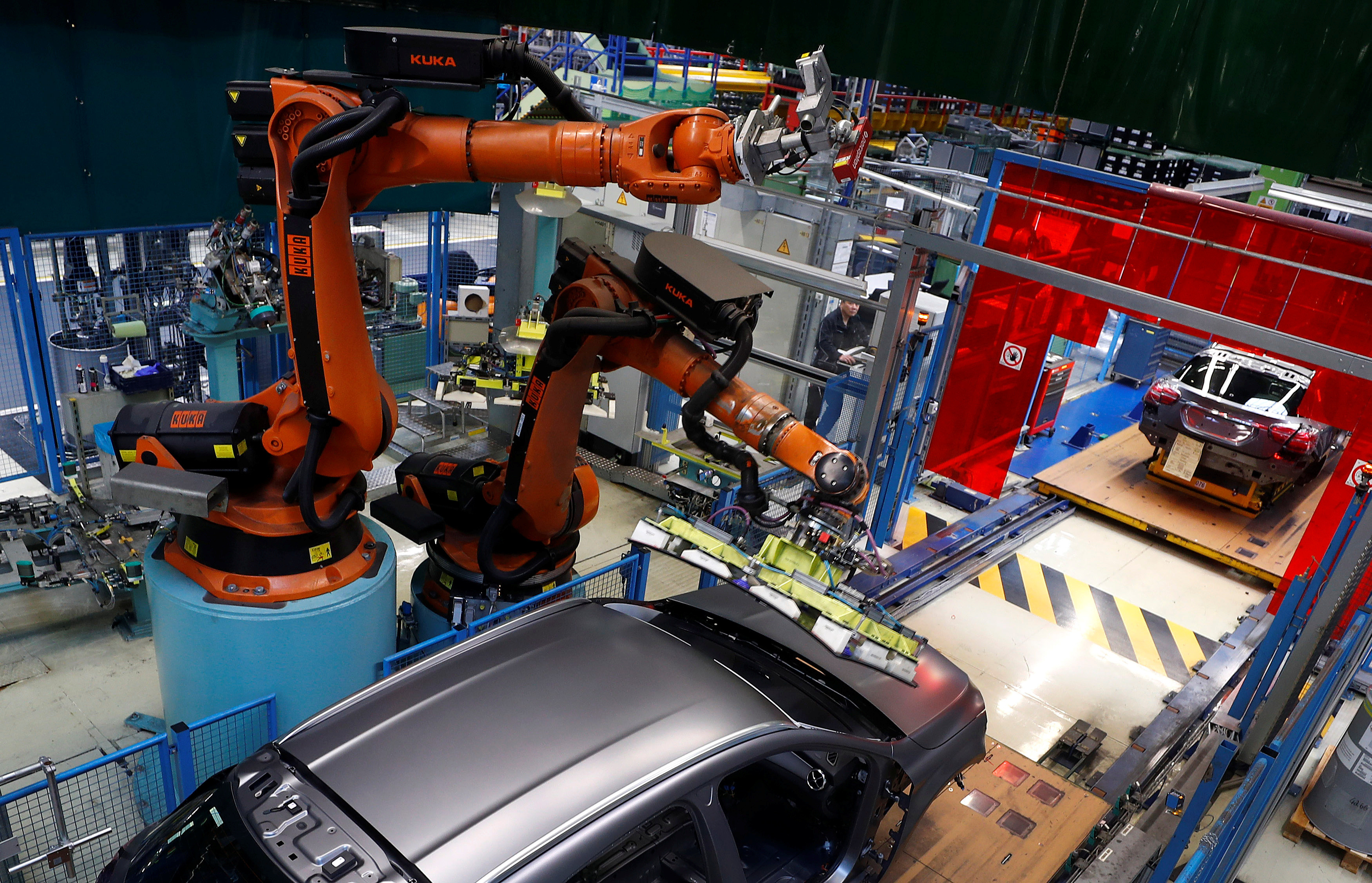 A robot engineered by Kuka adjusts a windscreen in a fully automated process on a model of the A-class production line of German car manufacturer Mercedes Benz at the Daimler factory in Rastatt, Germany, February 4, 2019. Picture taken on February 4, 2019.  REUTERS/Kai Pfaffenbach - RC18ED249E90