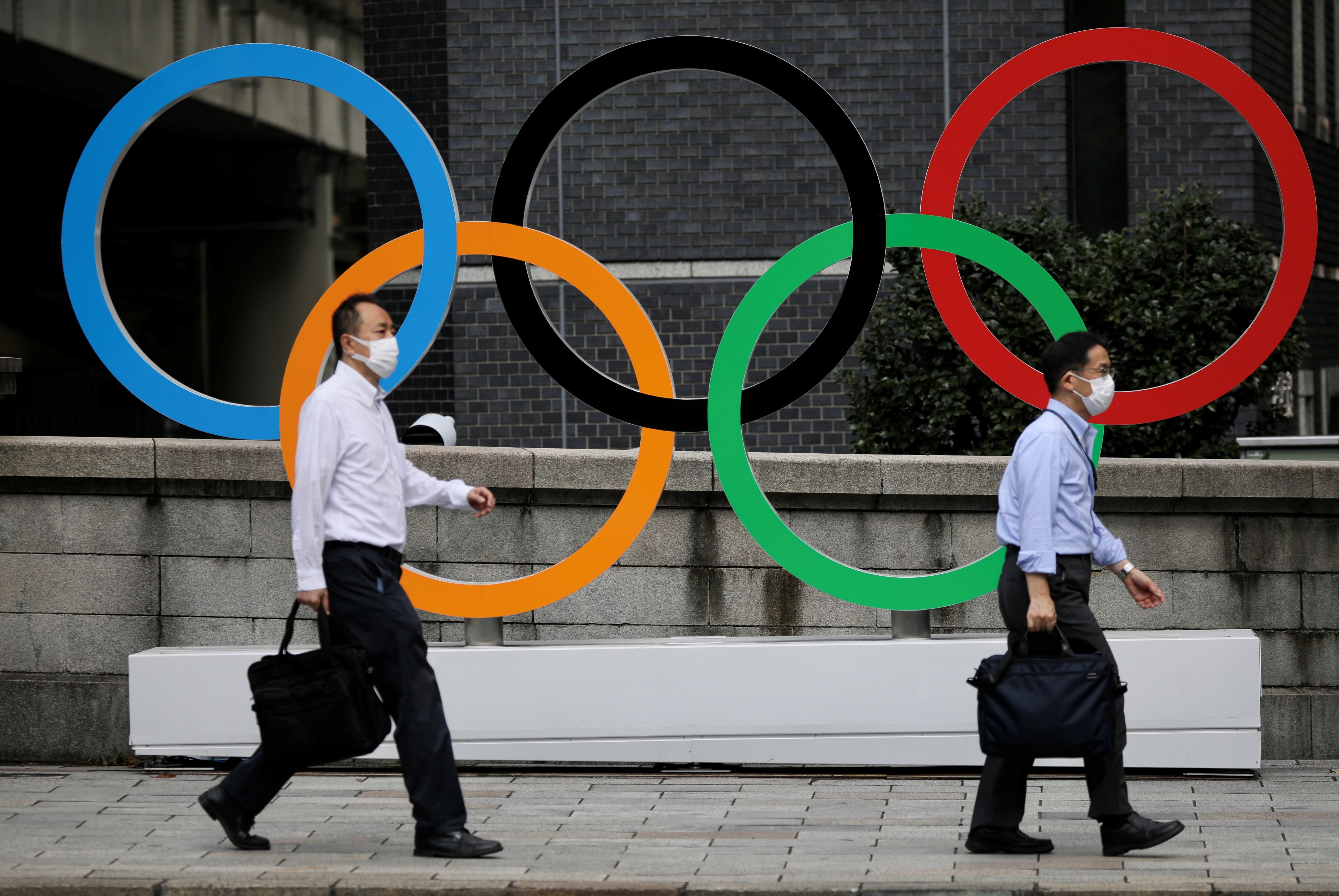 Men walk past the Olympic Rings in the commercial district of Nihonbashi during the Olympic games amid the coronavirus disease (COVID-19) outbreak in Tokyo, Japan August 4, 2021.    REUTERS/Kevin Coombs - RC2ZXO9V3VL1