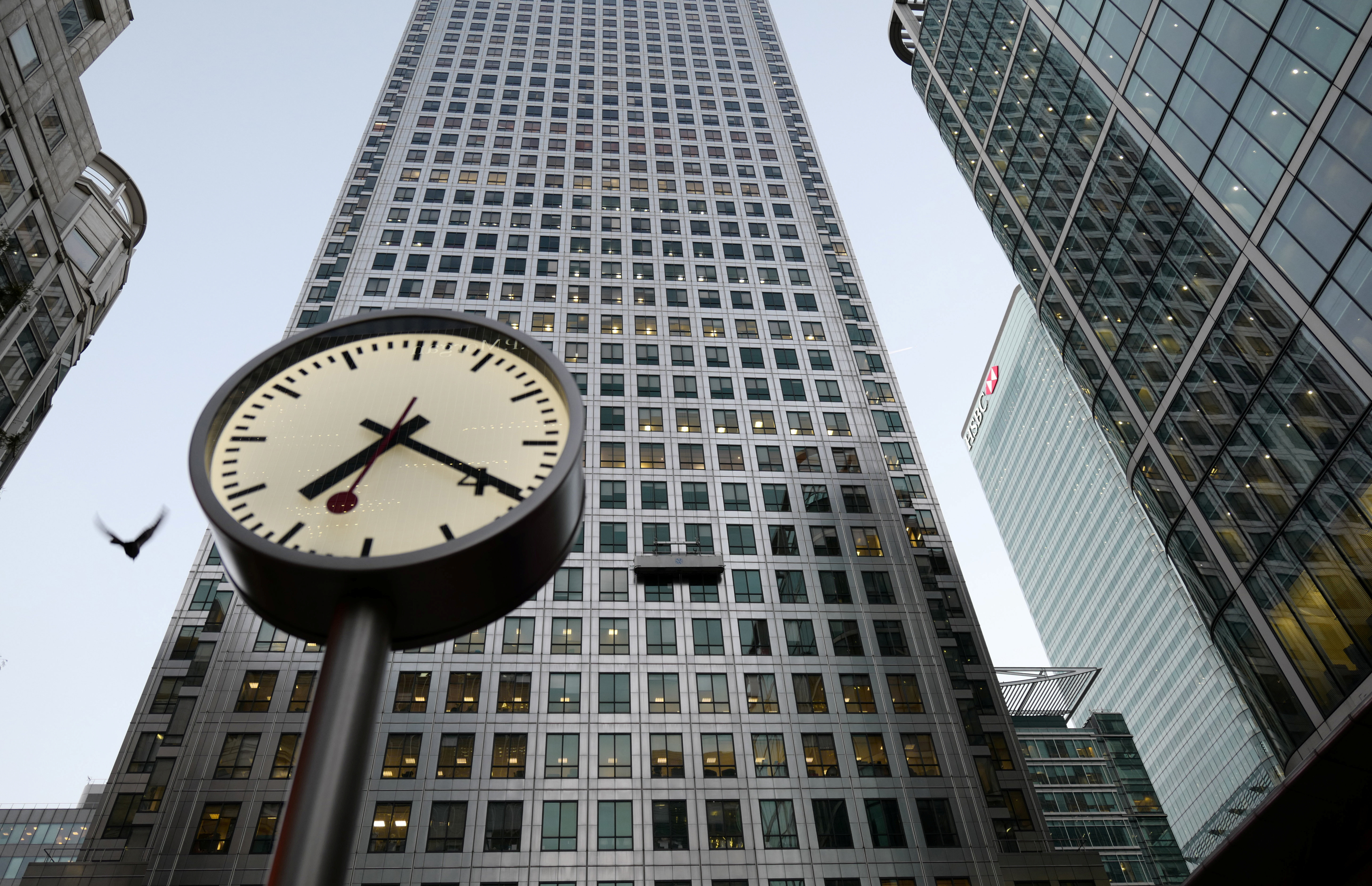 In front of HSBC's London headquarters, a bird flies past a clock as window cleaners work in London's Canary Wharf Financial District in London, Britain, October 11, 2016.   REUTERS/Russell Boyce - RTSRRJS