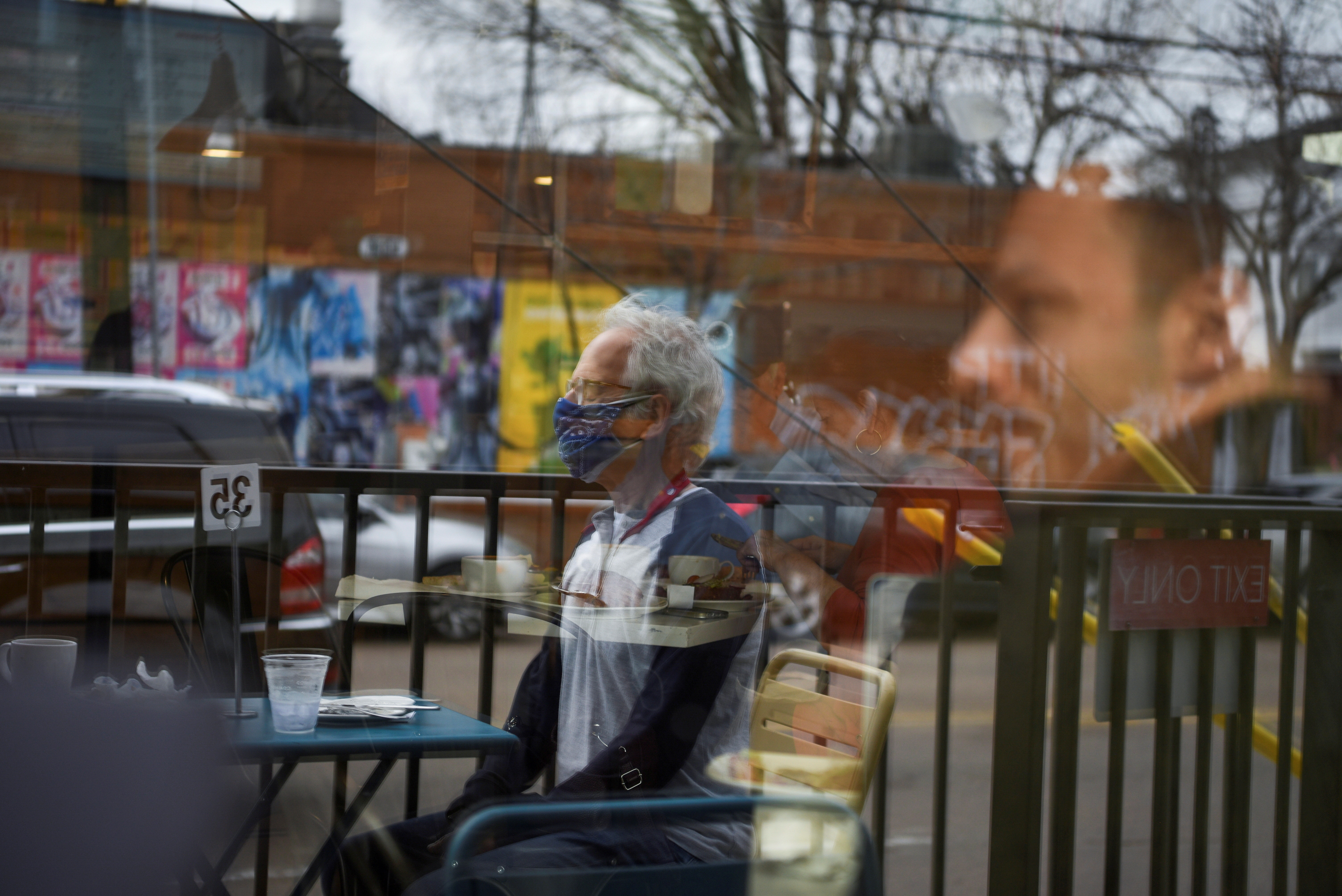 a man sits outside a cafe with a face mask on