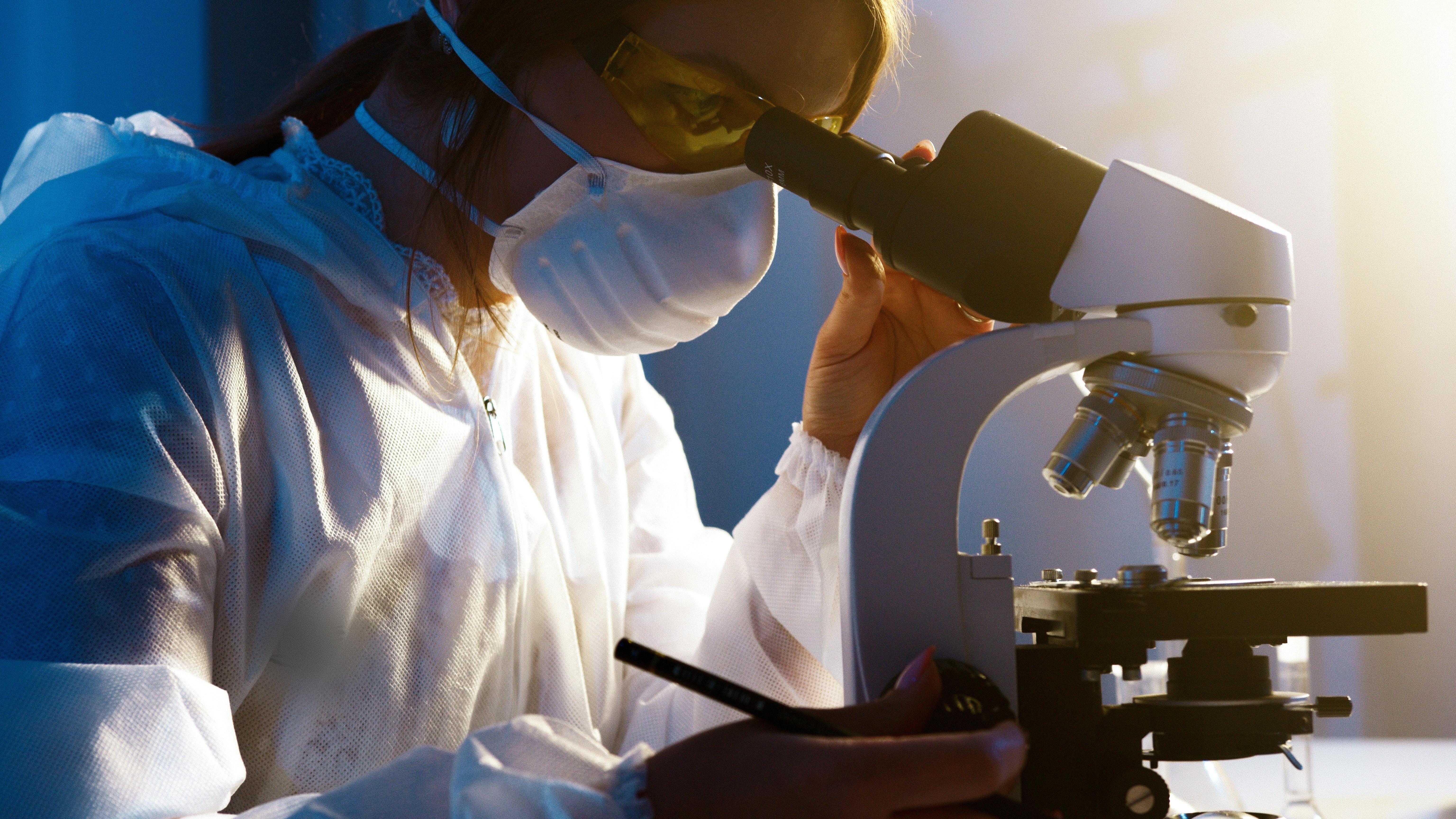 Woman wearing mask looking into microscope.